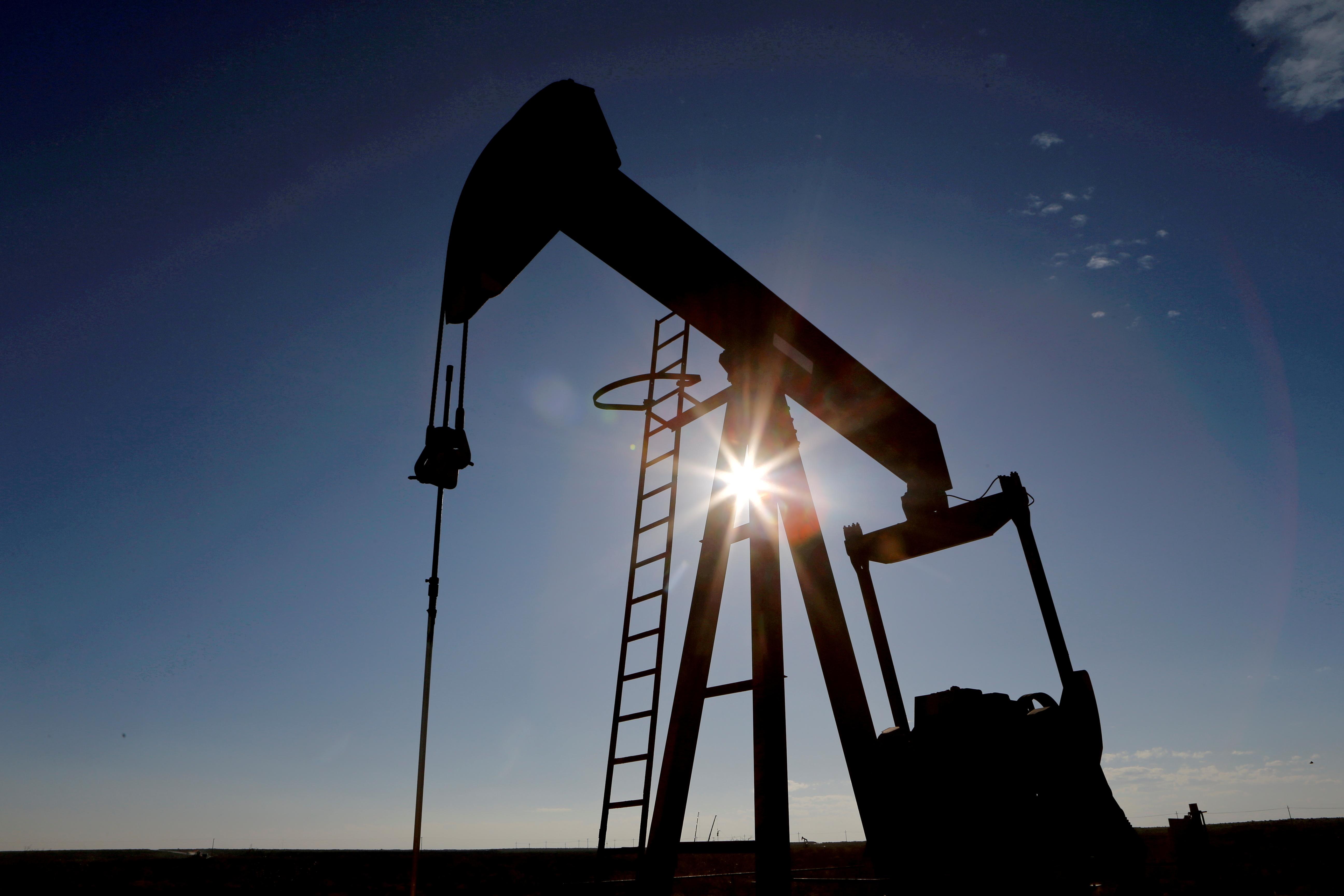 Le soleil derrière une grue pompant du pétrole brut dans le bassin permien du comté de Loving, Texas, États-Unis, le 22 novembre 2019. REUTERS/Angus Mordant/File Photo