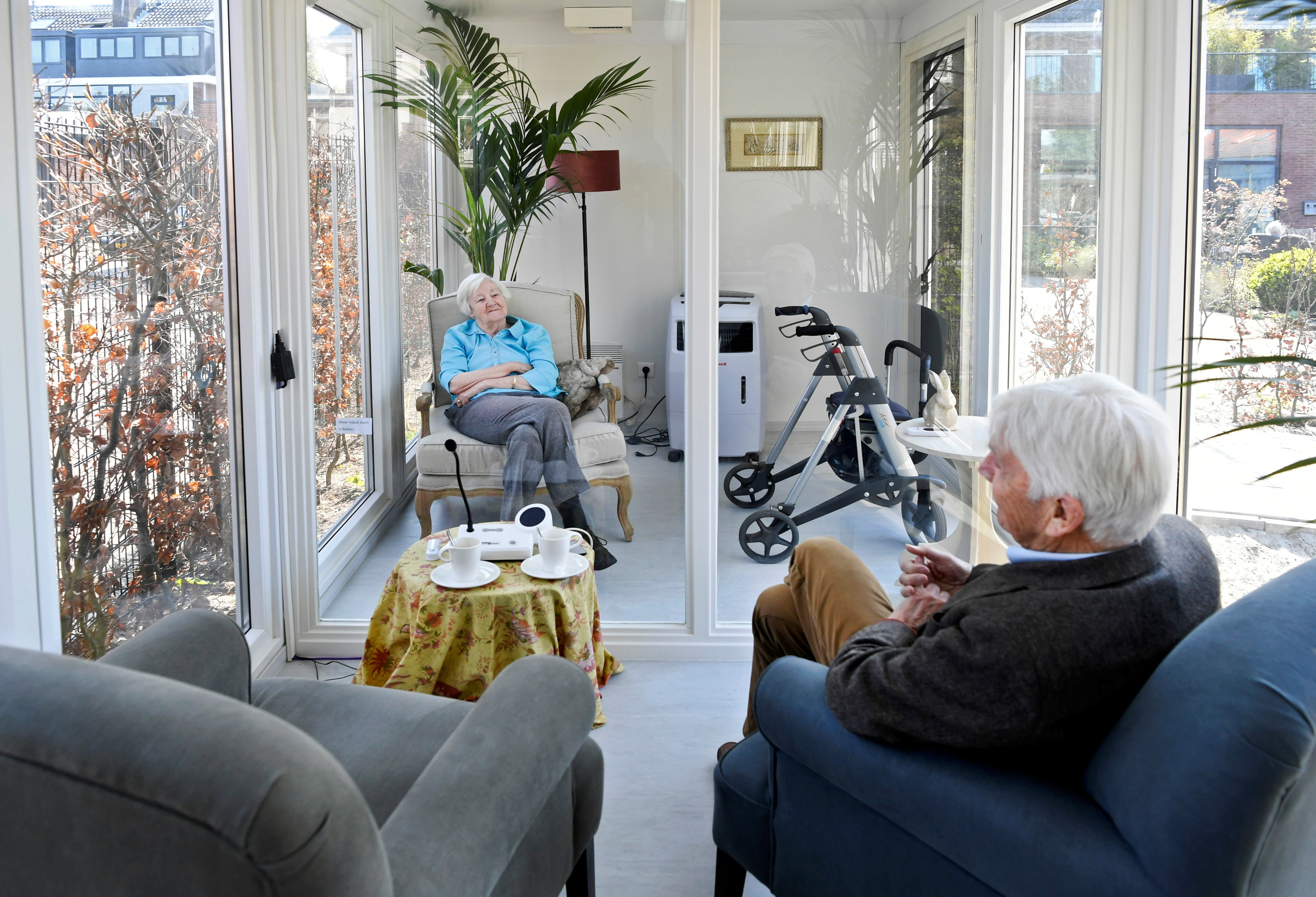 A man visits his wife at a care facility for elderly people with dementia in a glass house that has been built to combat loneliness   after a visit ban was imposed due to the coronavirus disease (COVID-19) outbreak in Wassenaar, Netherlands, April 9, 2020. REUTERS/Piroschka van de Wouw/File Photo