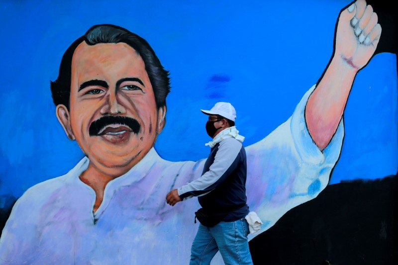 A man, wearing a face mask for protection against the coronavirus disease (COVID-19), walks by a mural depicting Nicaraguan President Daniel Ortega, in Managua, Nicaragua March 30, 2020. Picture taken March 30, 2020. REUTERS/Oswaldo Rivas/File Photo/File Photo/File Photo