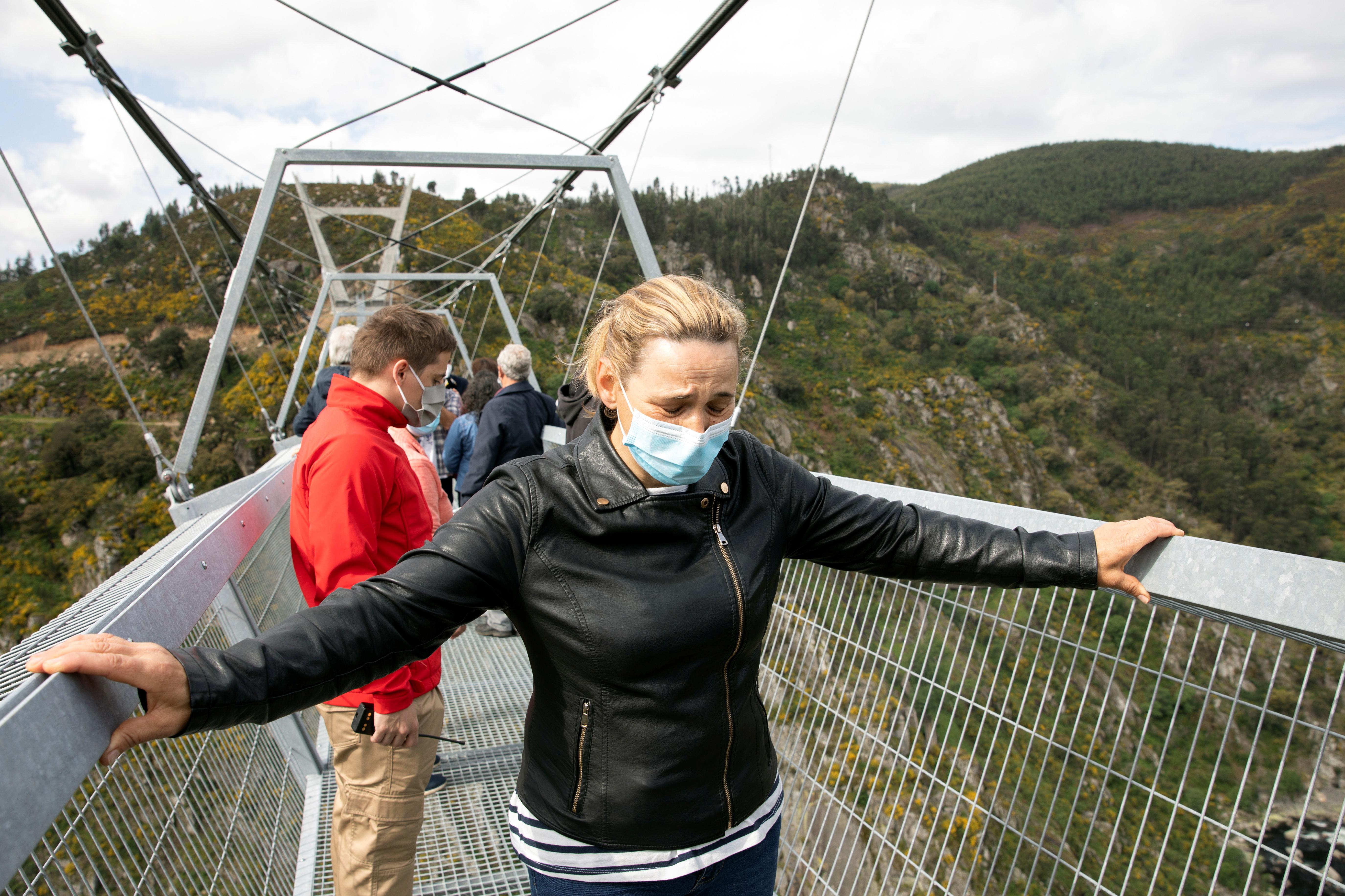 People walk on the world's longest pedestrian suspension bridge '516 Arouca', now open for local residents in Arouca, Portugal, April 29, 2021. REUTERS/Violeta Santos Moura