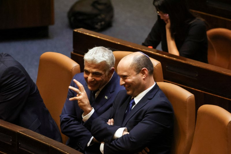 Prime Minister Naftali Bennett chats with Foreign Minister Yair Lapid, following the vote for the new coalition at the Knesset, Israel's parliament, in Jerusalem June 13, 2021. REUTERS/Ronen Zvulun