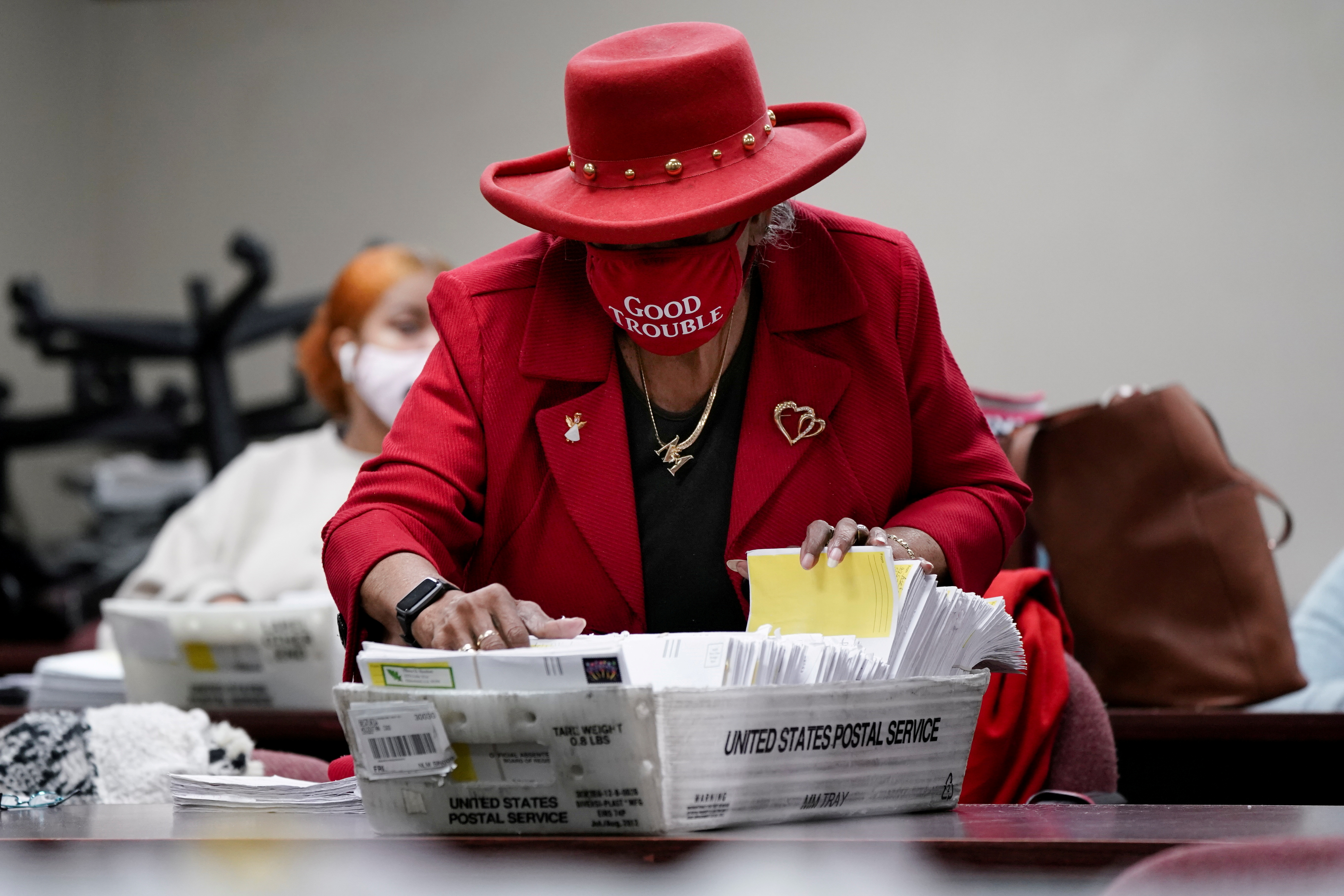 A DeKalb County election worker wearing a 'Good Trouble' facemask sorts empty absentee ballot envelopes following the U.S. Senate runoff elections in Decatur, Georgia, U.S., January 6, 2021.  REUTERS/Elijah Nouvelage/File Photo