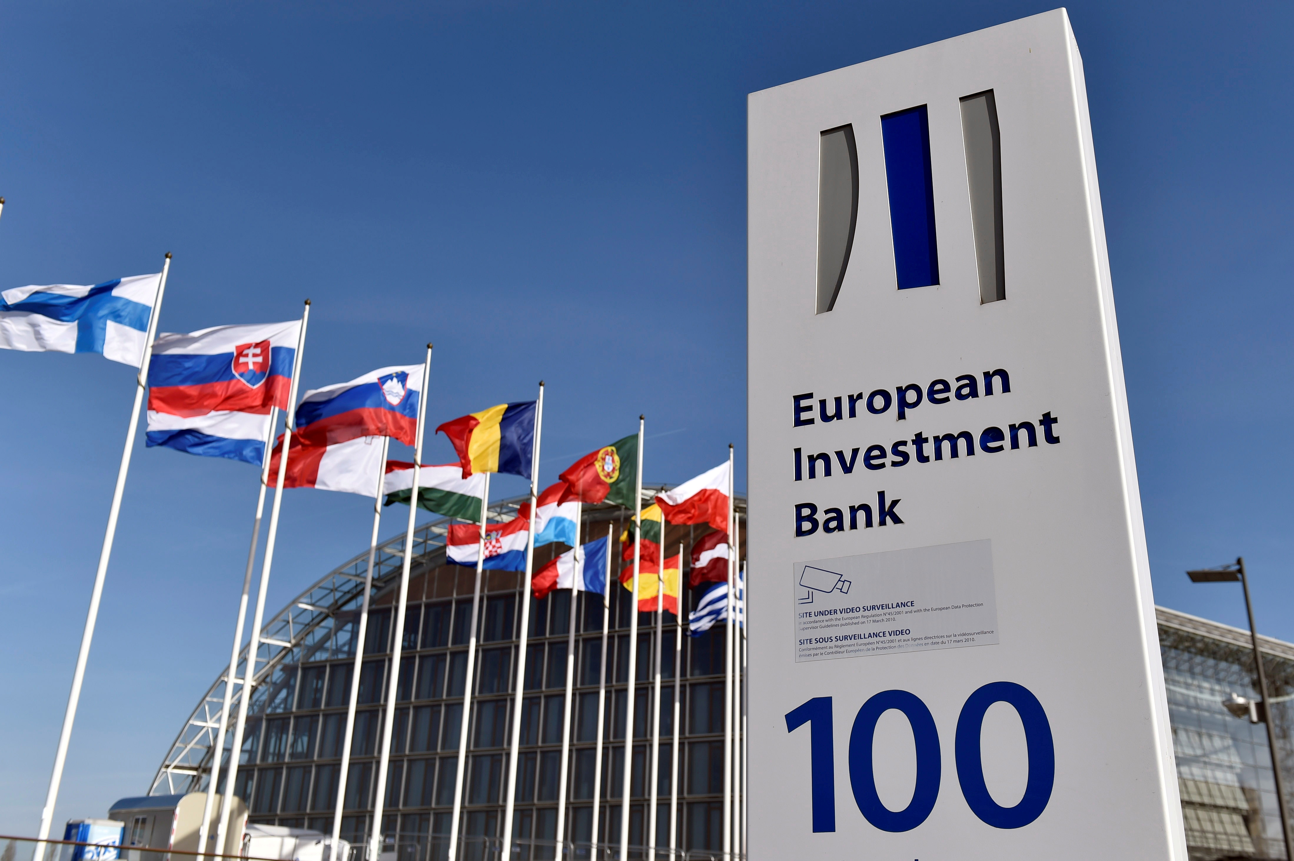 Flags are seen behind the logo of the European Investment Bank pictured in the city of Luxembourg, Luxembourg, March 25, 2017. Reuters/Eric Vidal/File Photo