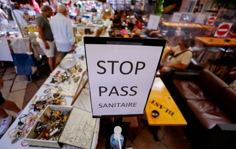 A coronavirus disease (COVID-19) health pass poster is seen in a restaurant as France brings on tougher restrictions where a proof of immunity will now be required to access most public spaces and to travel by inter-city train, in Nice, France, August 9, 2021. REUTERS/Eric Gaillard/File Photo