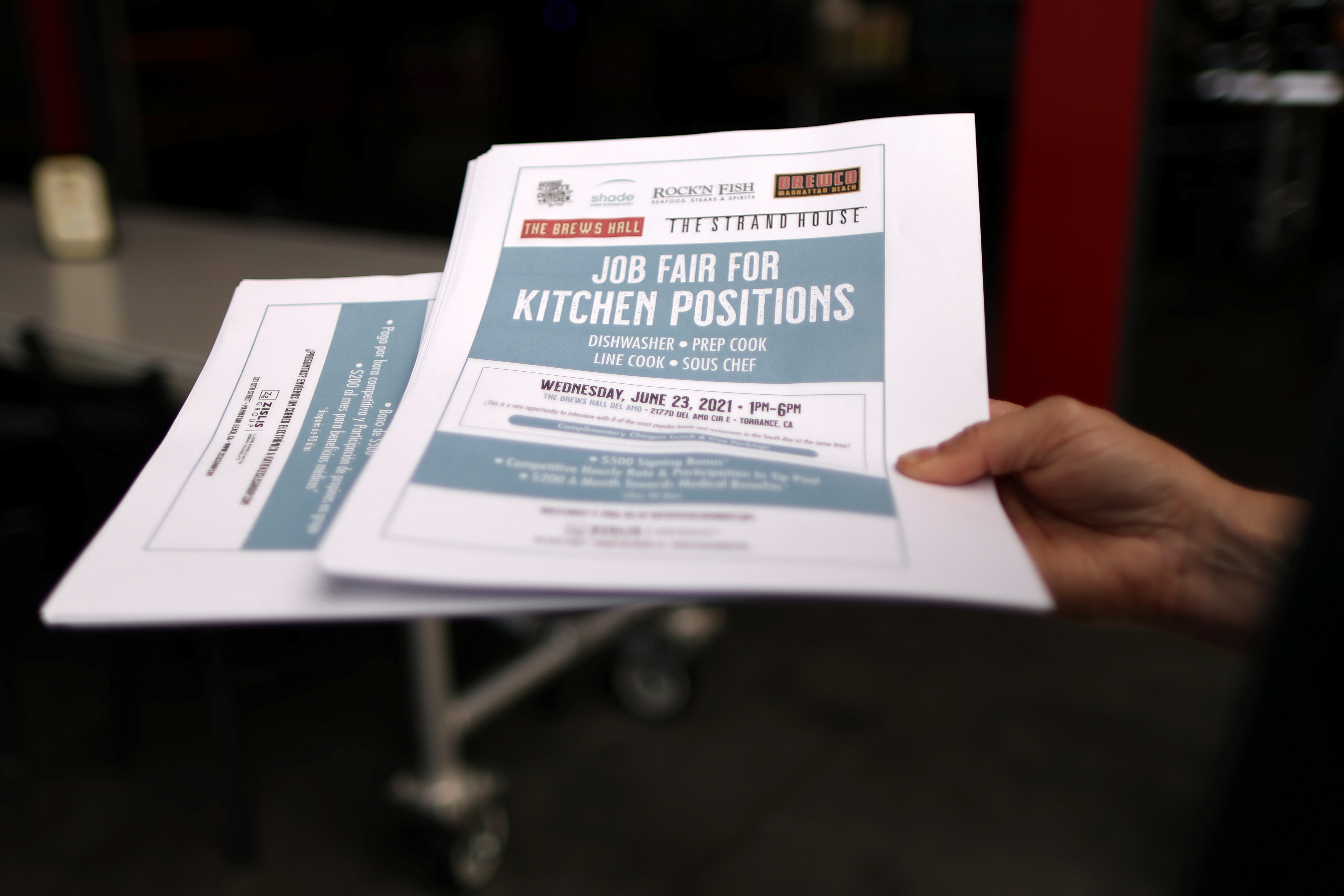 A woman holds fliers for a job fair for restaurant and hotel workers, after coronavirus disease (COVID-19) restrictions were lifted, in Torrance, near Los Angeles, California, U.S., June 23, 2021. REUTERS/Lucy Nicholson