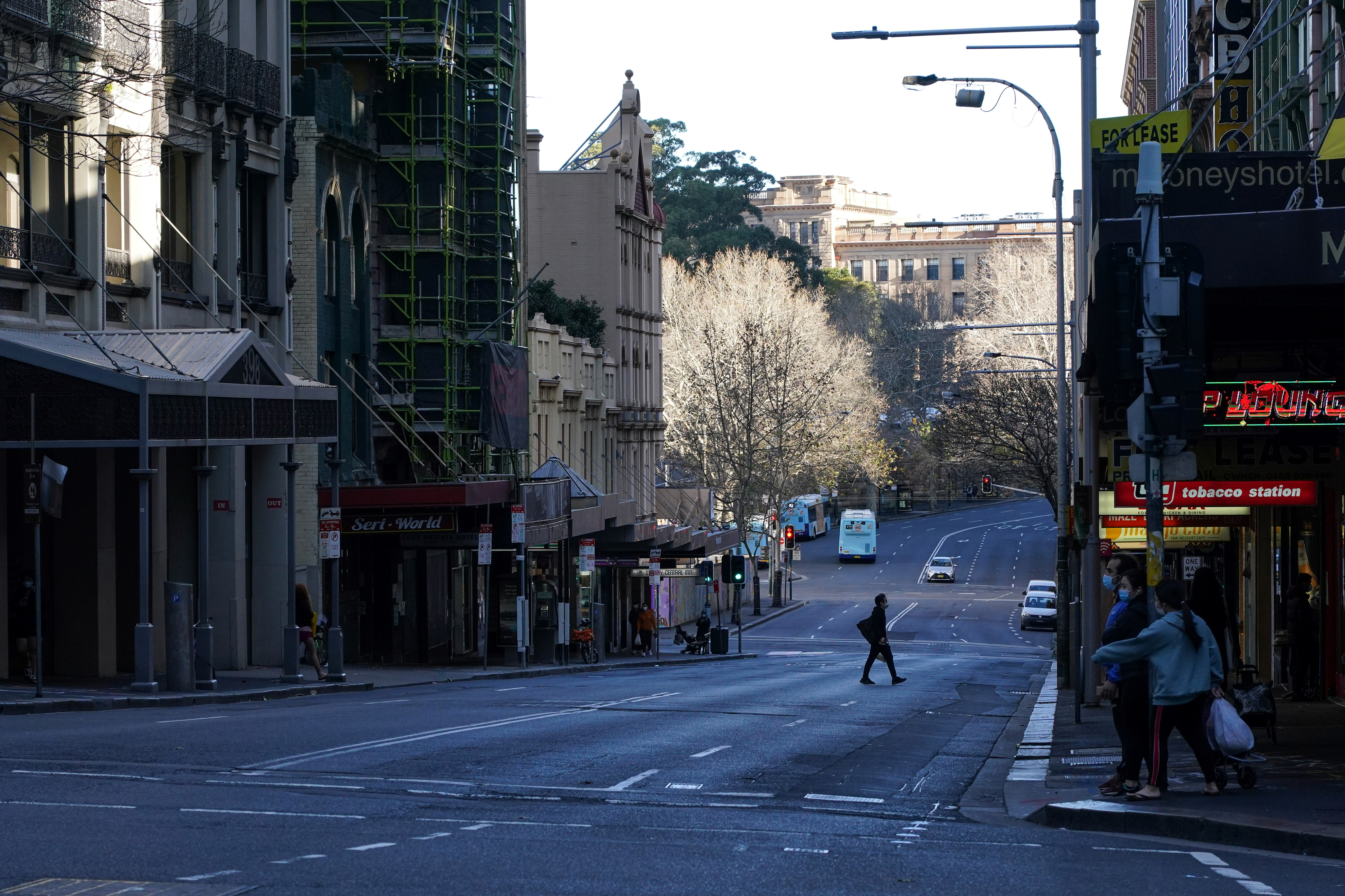 A pedestrian crosses an almost empty street in the City Centre during a lockdown to curb the spread of the coronavirus disease (COVID-19) outbreak in Sydney, Australia, July 21, 2021. REUTERS/Loren Elliott