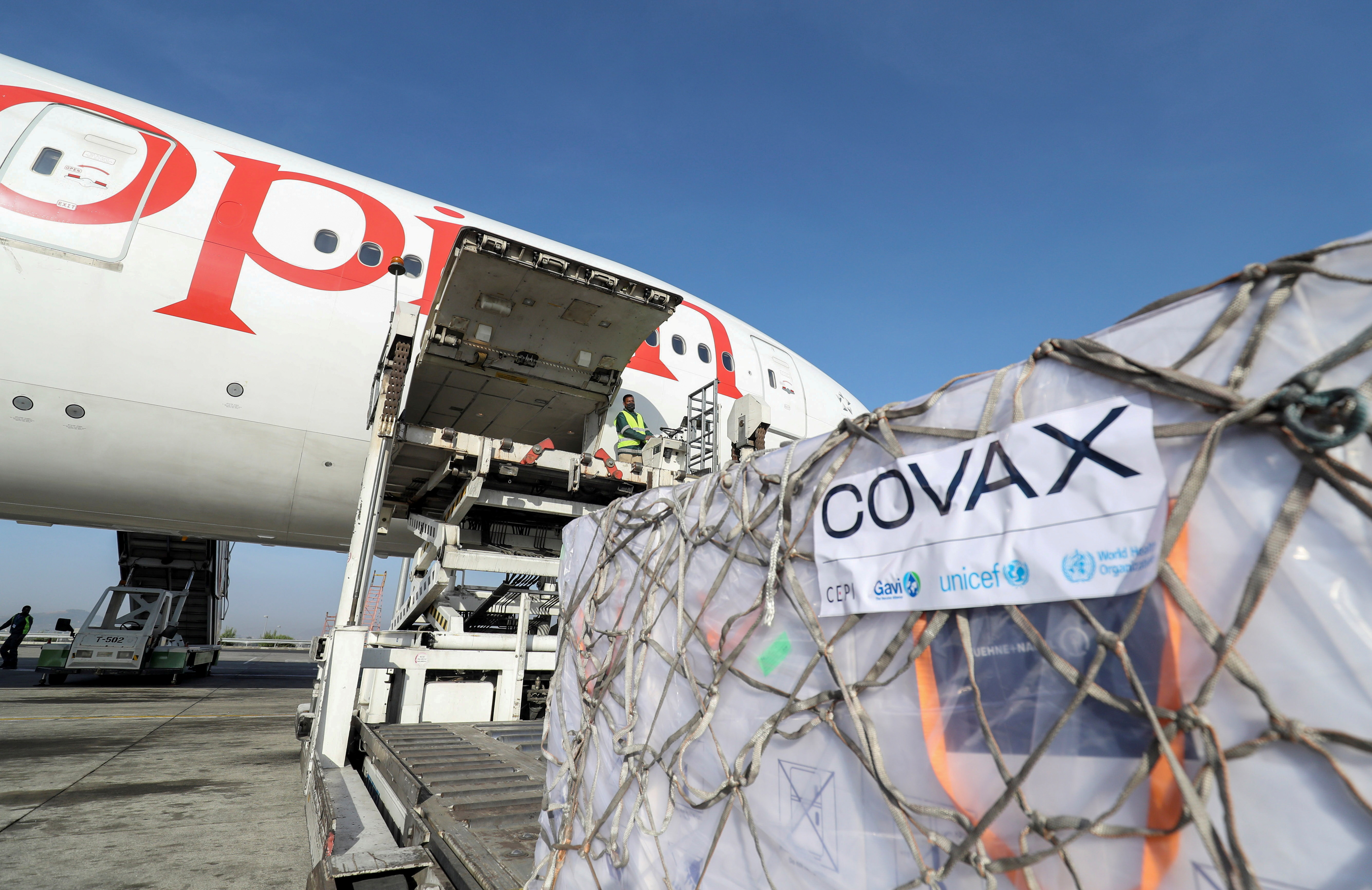 Ethiopian Airlines staff unload AstraZeneca/Oxford vaccines under the COVAX scheme against the coronavirus disease (COVID-19) from a cargo plane at Bole International Airport in Addis Ababa, Ethiopia, March 7, 2021. REUTERS/Tiksa Negeri/File Photo