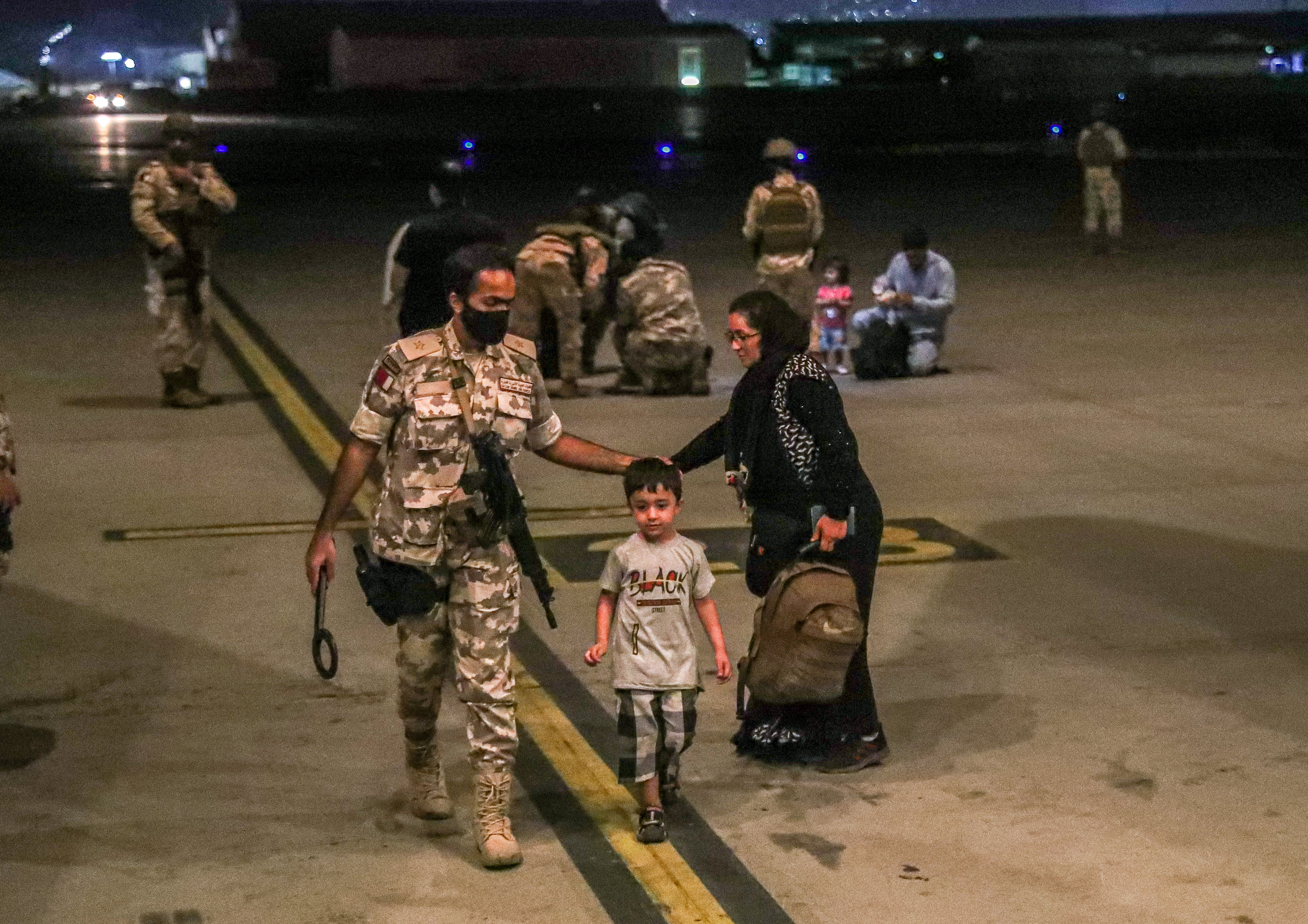 A member of the Qatar Air force walks next to a boy evacuated from Afghanistan, at Al-Udeid airbase in Doha, Qatar in this recent undated handout. Government Communications Office of the State of Qatar/Handout via REUTERS