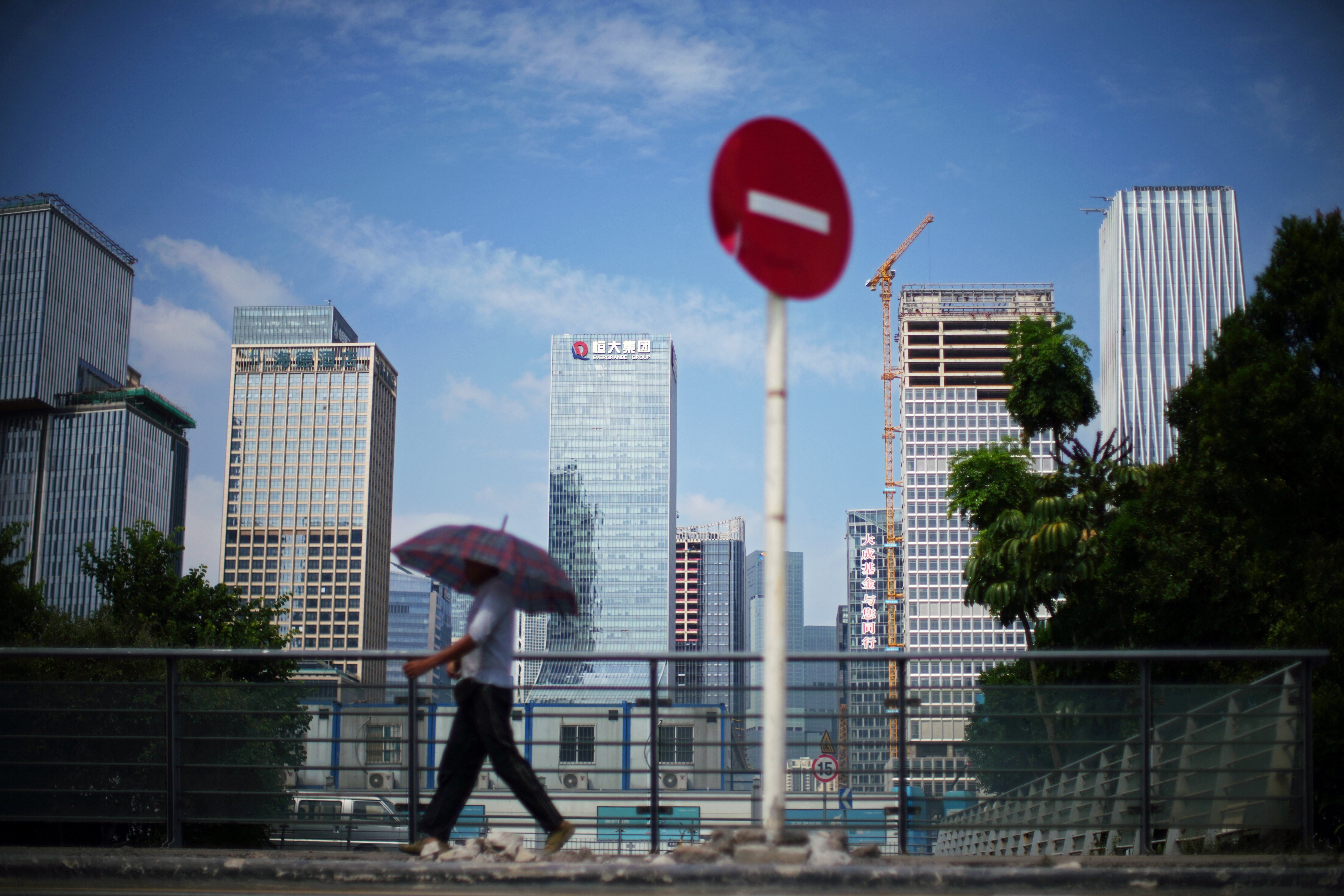A man walks past a No Entry traffic sign near the headquarters of China Evergrande Group in Shenzhen, Guangdong province, China September 26, 2021. REUTERS/Aly Song/Files