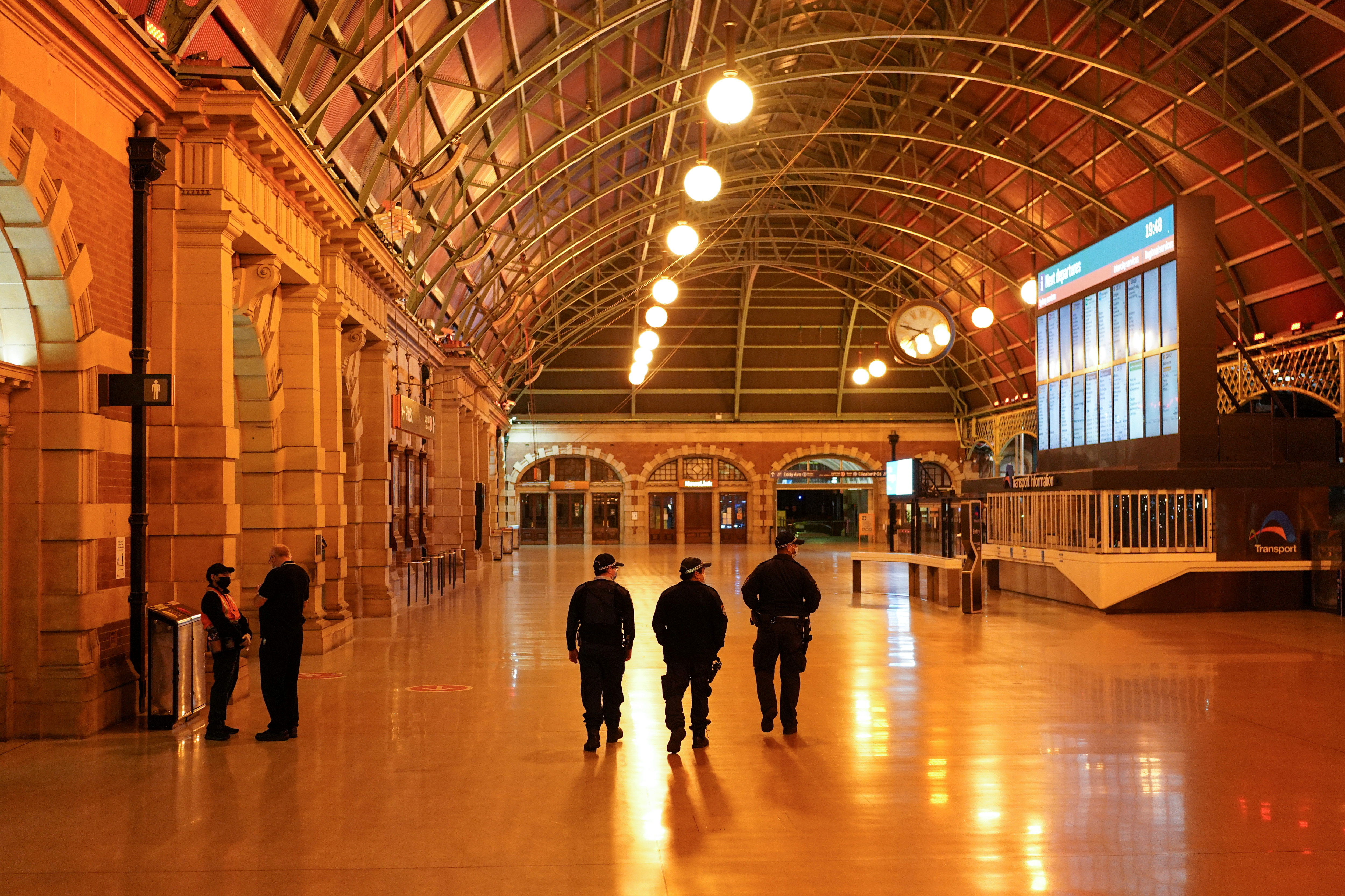 Police officers patrol through the quiet Central Station in the city centre during a lockdown to curb the spread of a coronavirus disease (COVID-19) outbreak in Sydney, Australia, August 12, 2021.  REUTERS/Loren Elliott
