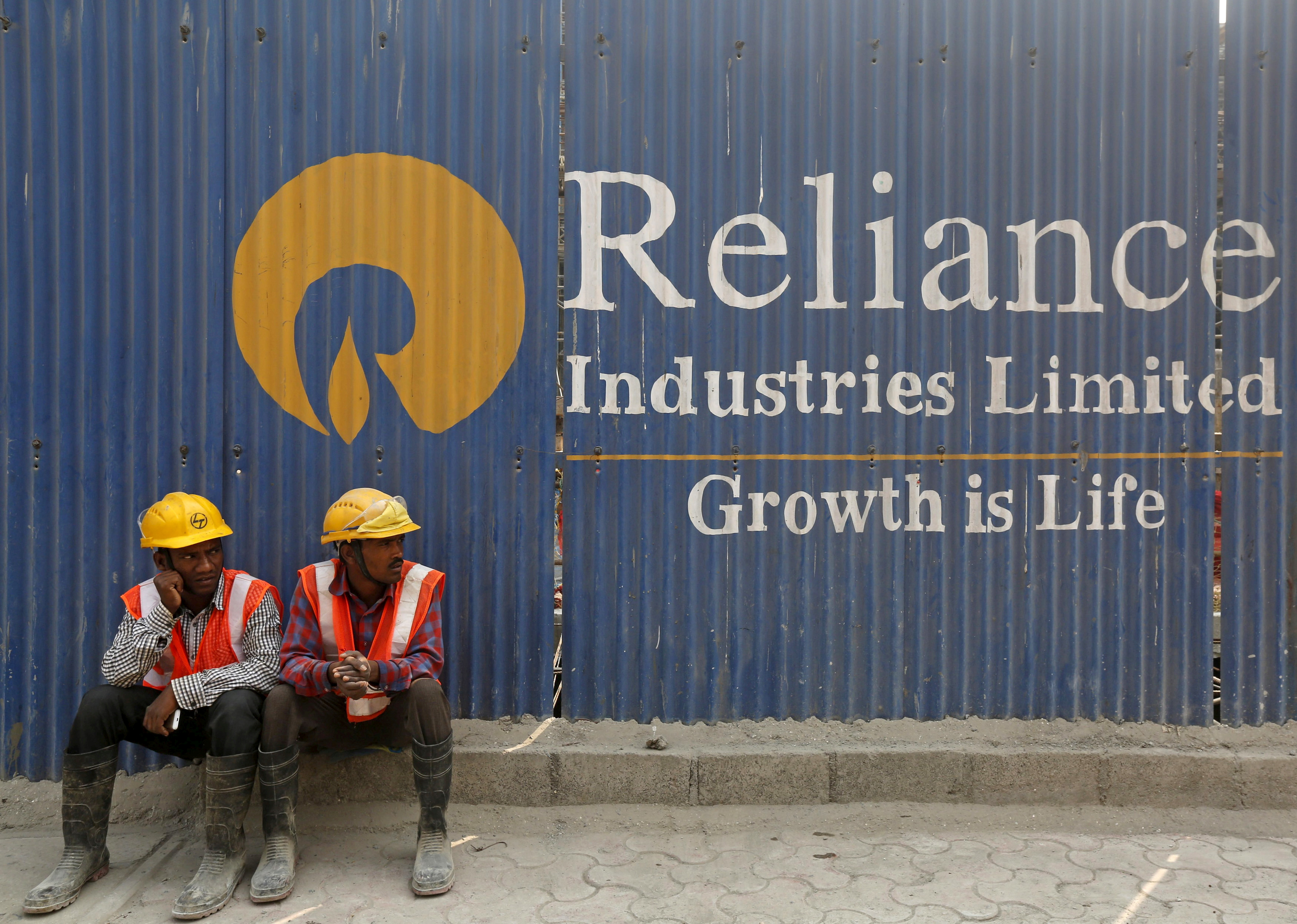 Labourers rest in front of an advertisement of Reliance Industries Limited at a construction site in Mumbai, India, March 2, 2016. REUTERS/Shailesh Andrade/File Photo