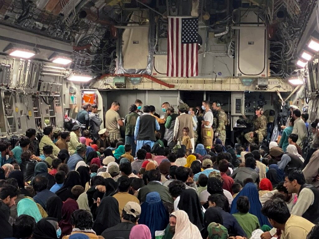 A newborn baby is looked after prior taking off with other Afghan evacuees on a C-17 Globemaster III at a Middle East staging area August 23, 2021. U.S. Air Force//Handout via REUTERS