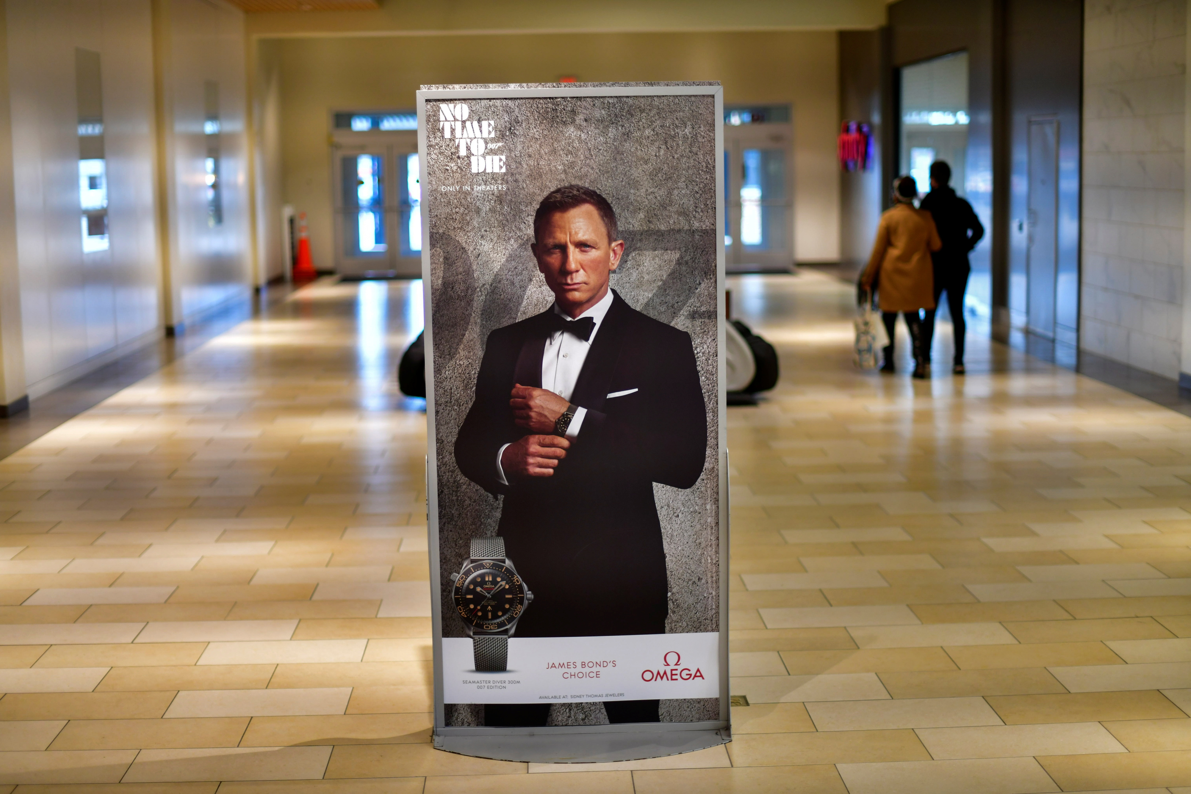Shoppers walk past an advertisement for the upcoming James Bond film