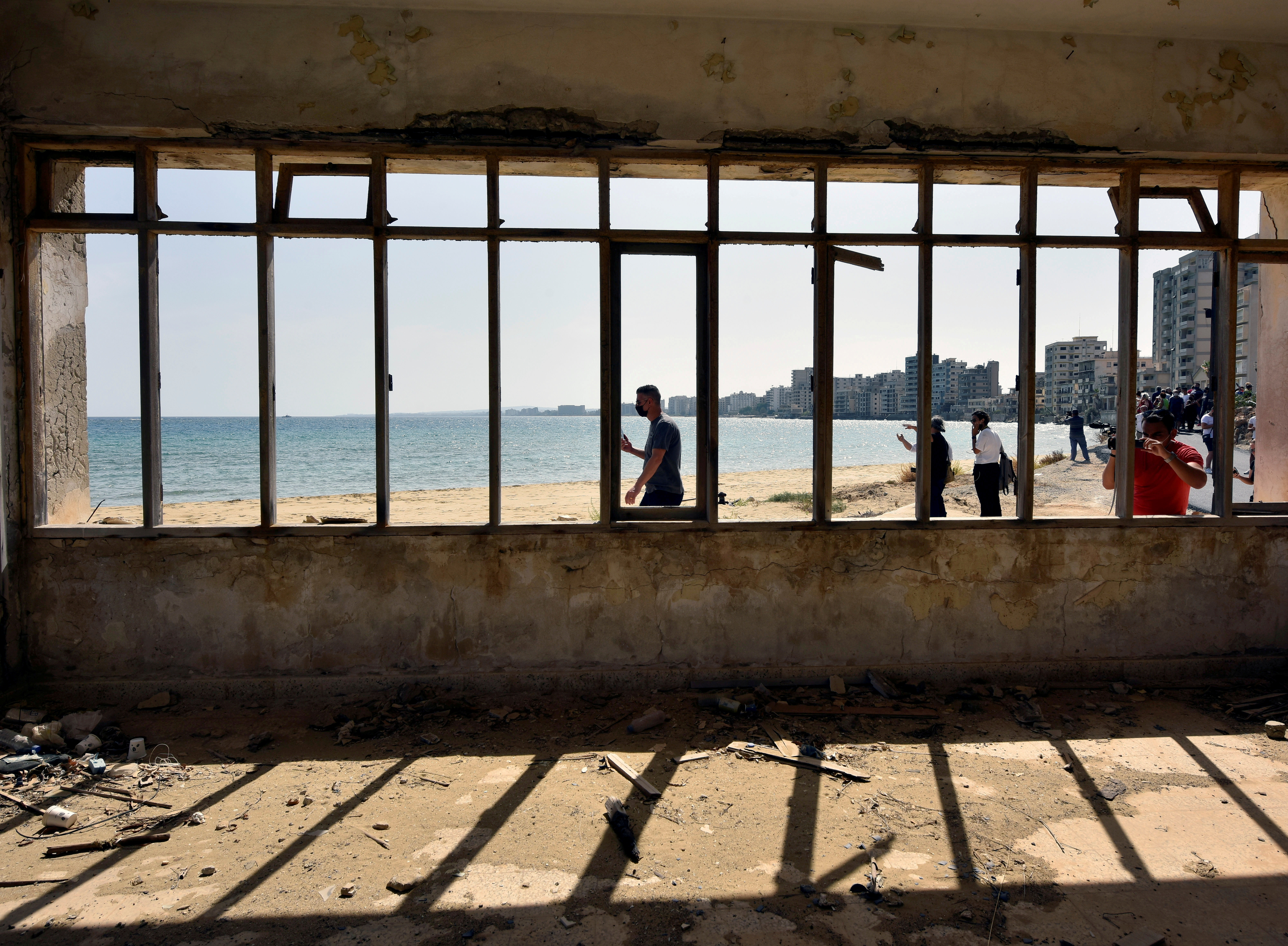 People walk on a beach inside an area fenced off by the Turkish military since 1974 in the abandoned coastal area of Varosha, a suburb of the town of Famagusta in Turkish-controlled northern Cyprus, October 8, 2020. REUTERS/Harun Ucar/File Photo
