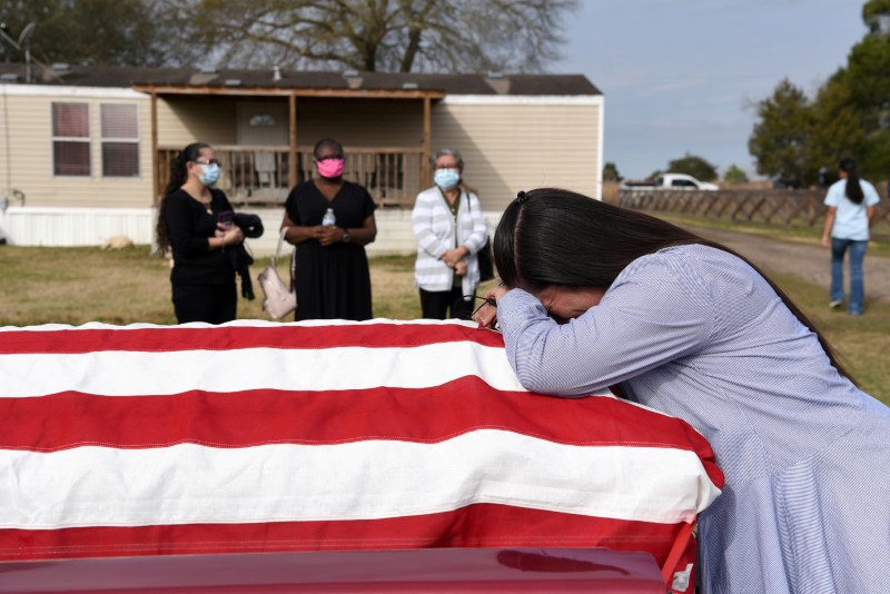 Lila Blanks holds the casket of her husband, Gregory Blanks, 50, who died of the coronavirus disease (COVID-19), ahead of his funeral in San Felipe, Texas, U.S., January 26, 2021.  REUTERS/Callaghan O'Hare/File Photo