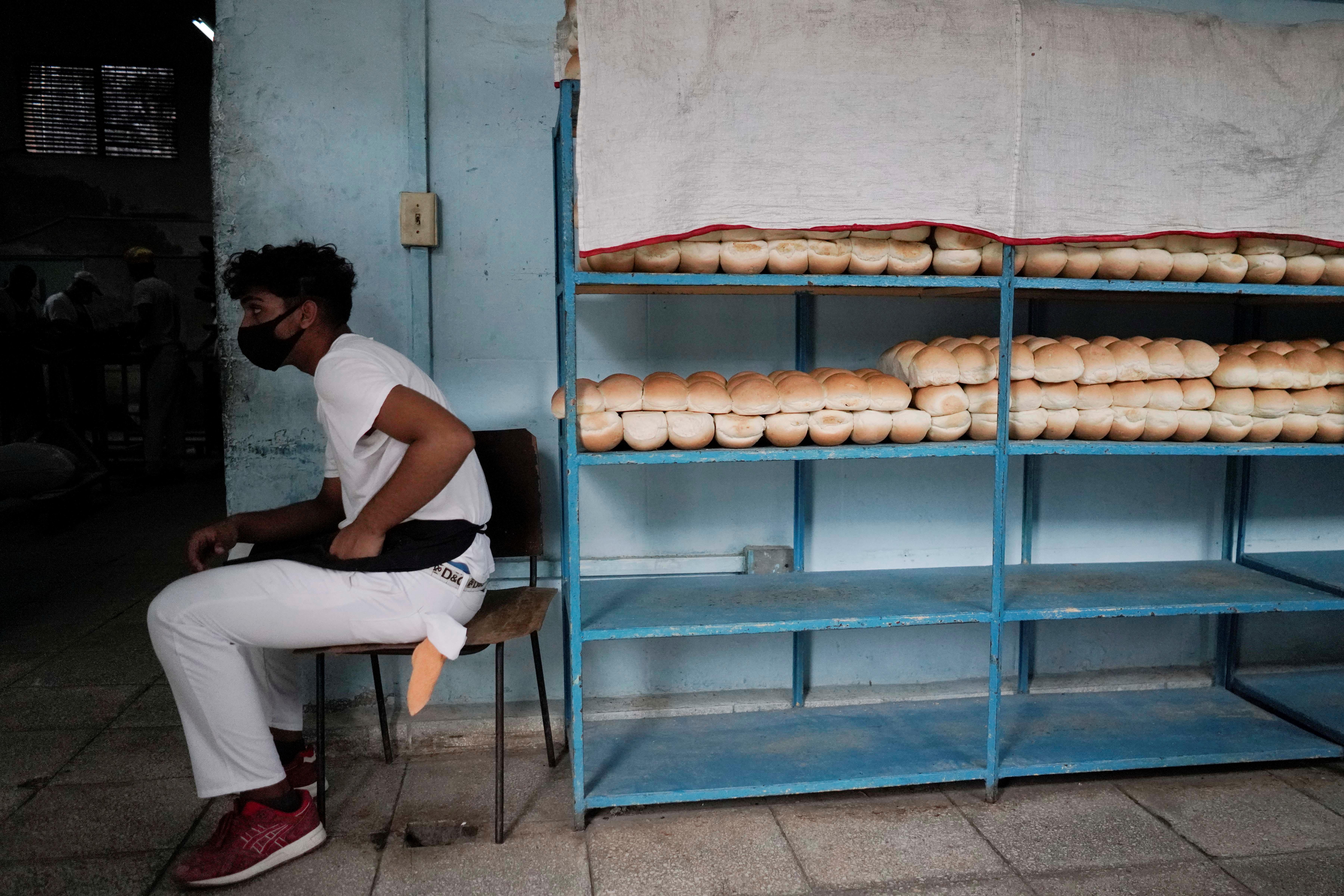 An employee sits beside bread stored on shelves inside a bakery in Havana, Cuba, May 18, 2021. Picture taken on May 18, 2021. REUTERS/Alexandre Meneghini
