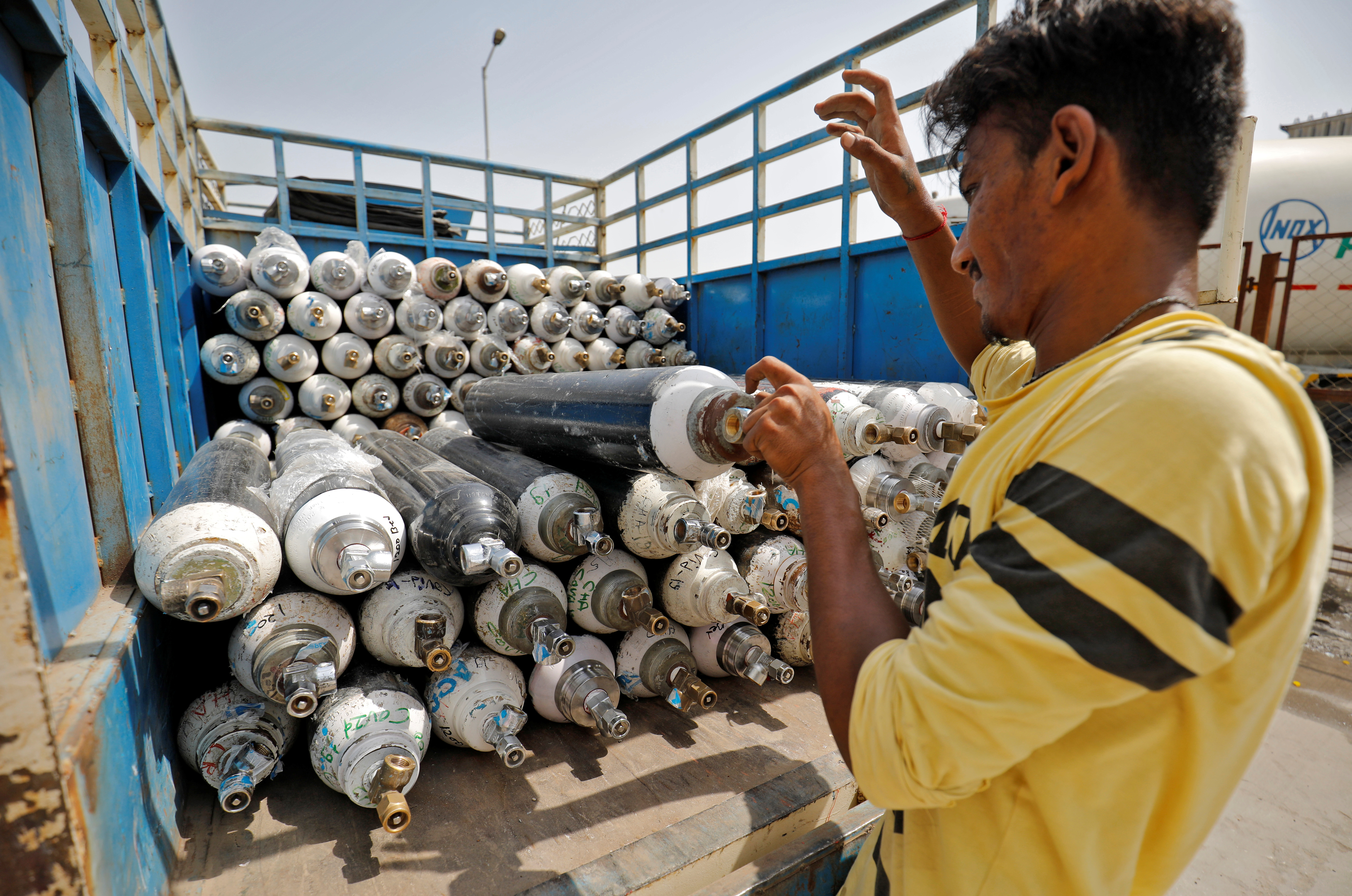 A worker loads empty oxygen cylinders onto a supply van to be transported to a filling station, at a COVID-19 hospital, amidst the spread of the coronavirus disease (COVID-19) in Ahmedabad, India, April 22, 2021. REUTERS/Amit Dave