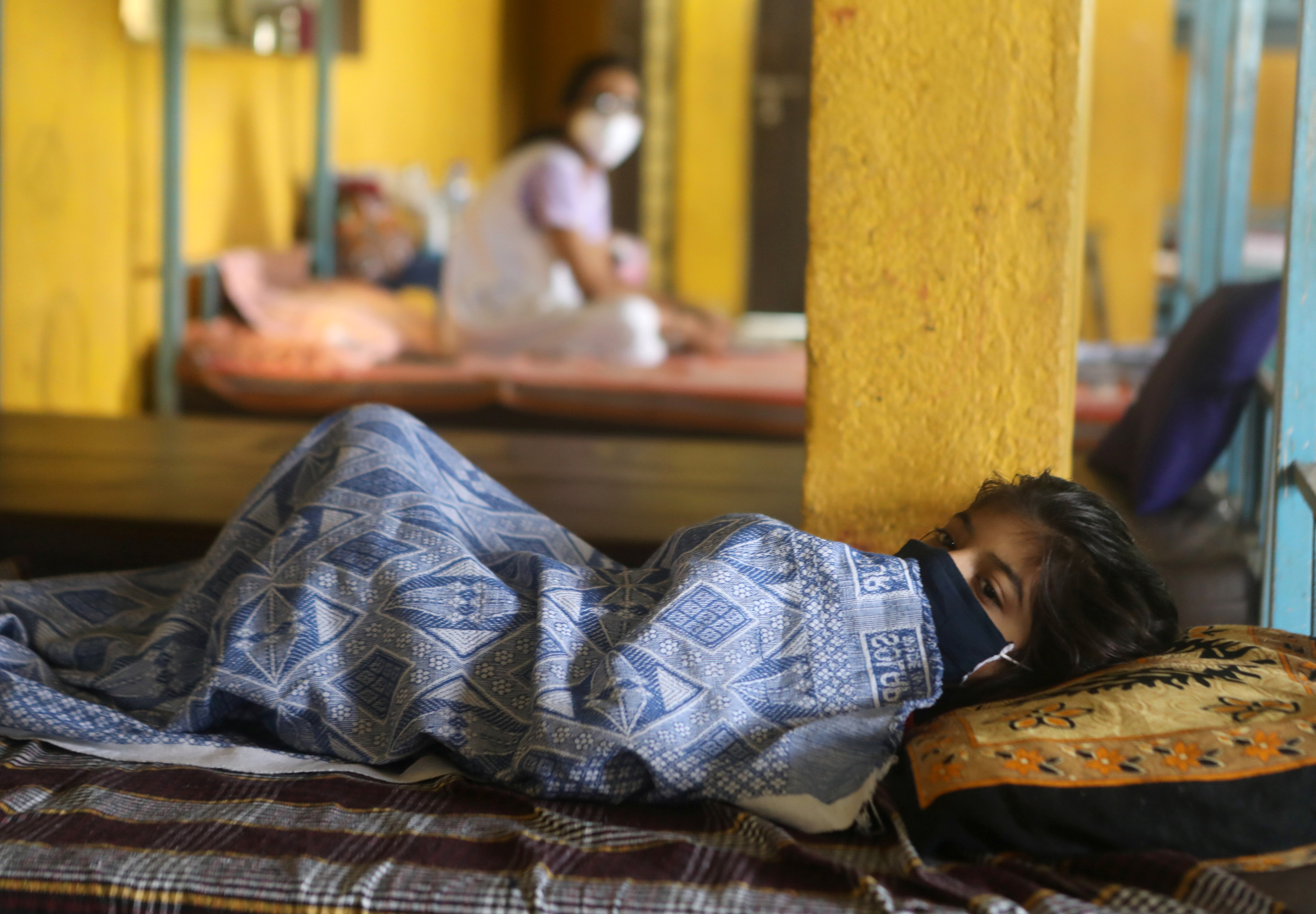 A patient suffering from coronavirus disease (COVID-19) rests inside a classroom turned COVID-19 care facility on the outskirts of Mumbai, India, May 24, 2021. REUTERS/Francis Mascarenhas/File Photo