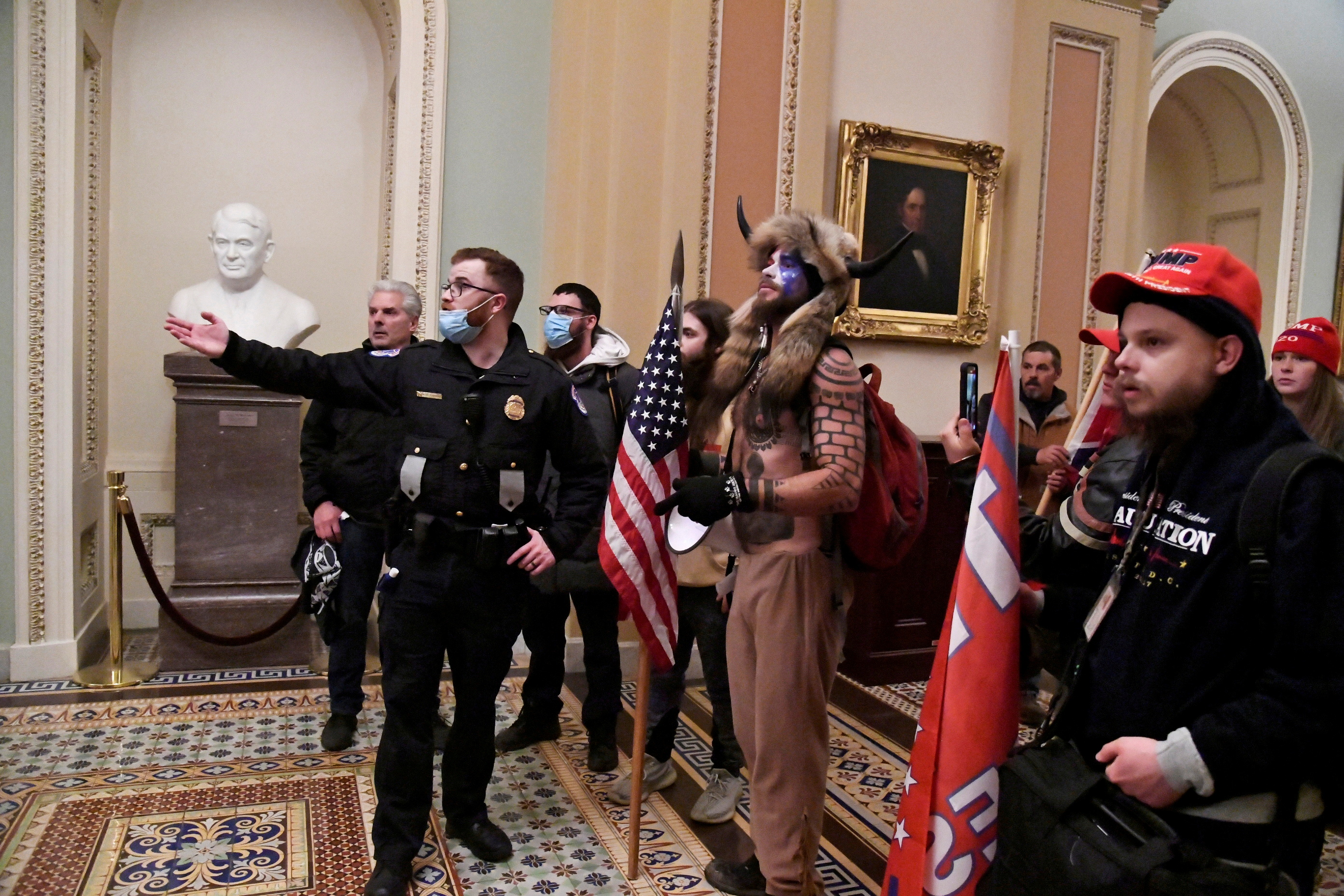 Police speak to supporters of U.S. President Donald Trump, including Jacob Chansley, also known as Jake Angeli, in the horn and fur costume, as they demonstrate on the second floor of the U.S. Capitol near the entrance to the Senate after breaching security defenses, in Washington, U.S., January 6, 2021. Picture taken January 6, 2021.        REUTERS/Mike Theiler