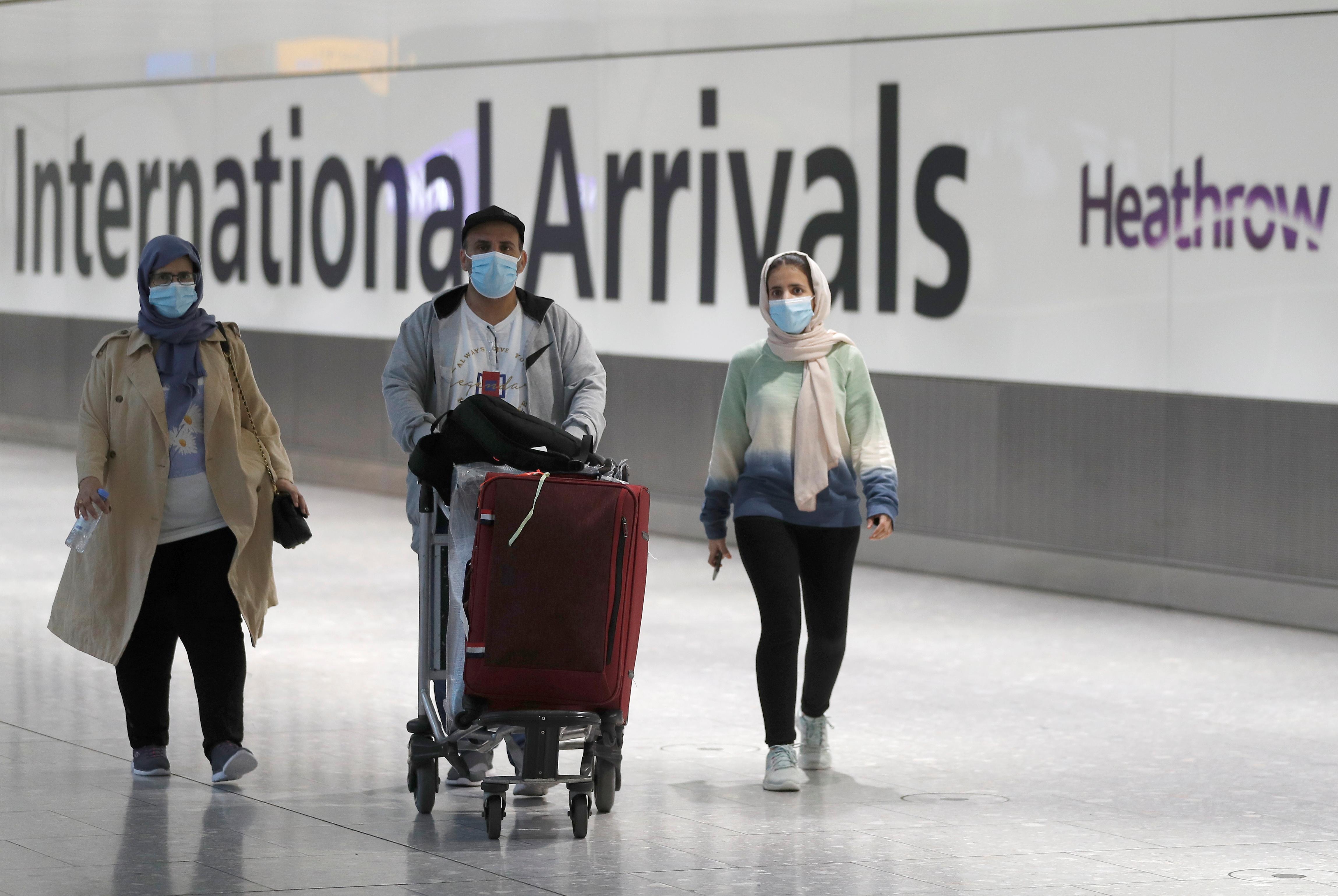 Passengers walk through the International arrivals area of Terminal 5 in London's Heathrow Airport, Britain, August 2, 2021.  REUTERS/Peter Nicholls