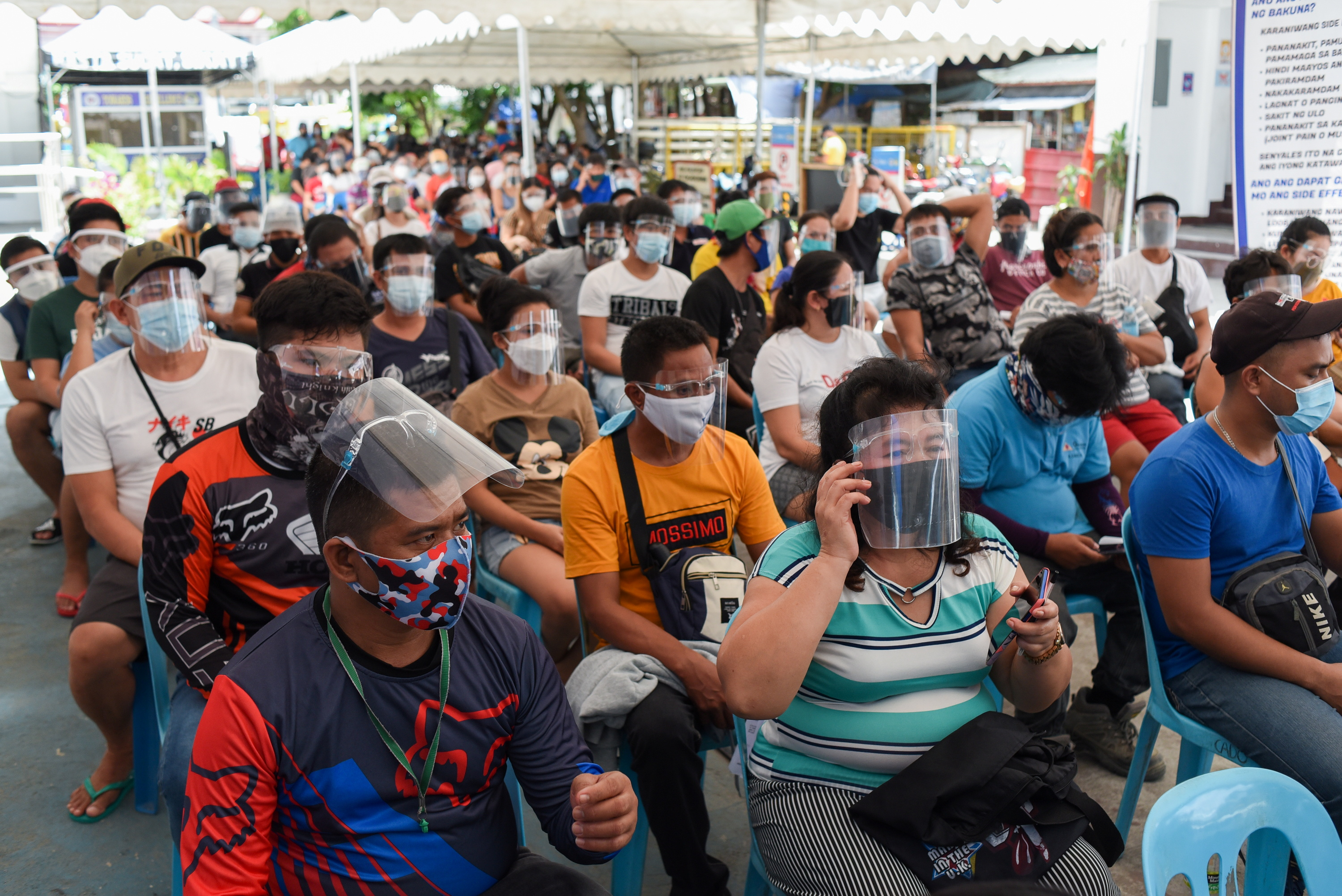 Residents wearing face masks as protection against the coronavirus disease (COVID-19) queue for vaccines, at the Barangay Sucat Covered Court, in Muntinlupa City, Metro Manila, Philippines, June 21, 2021. REUTERS/Lisa Marie David
