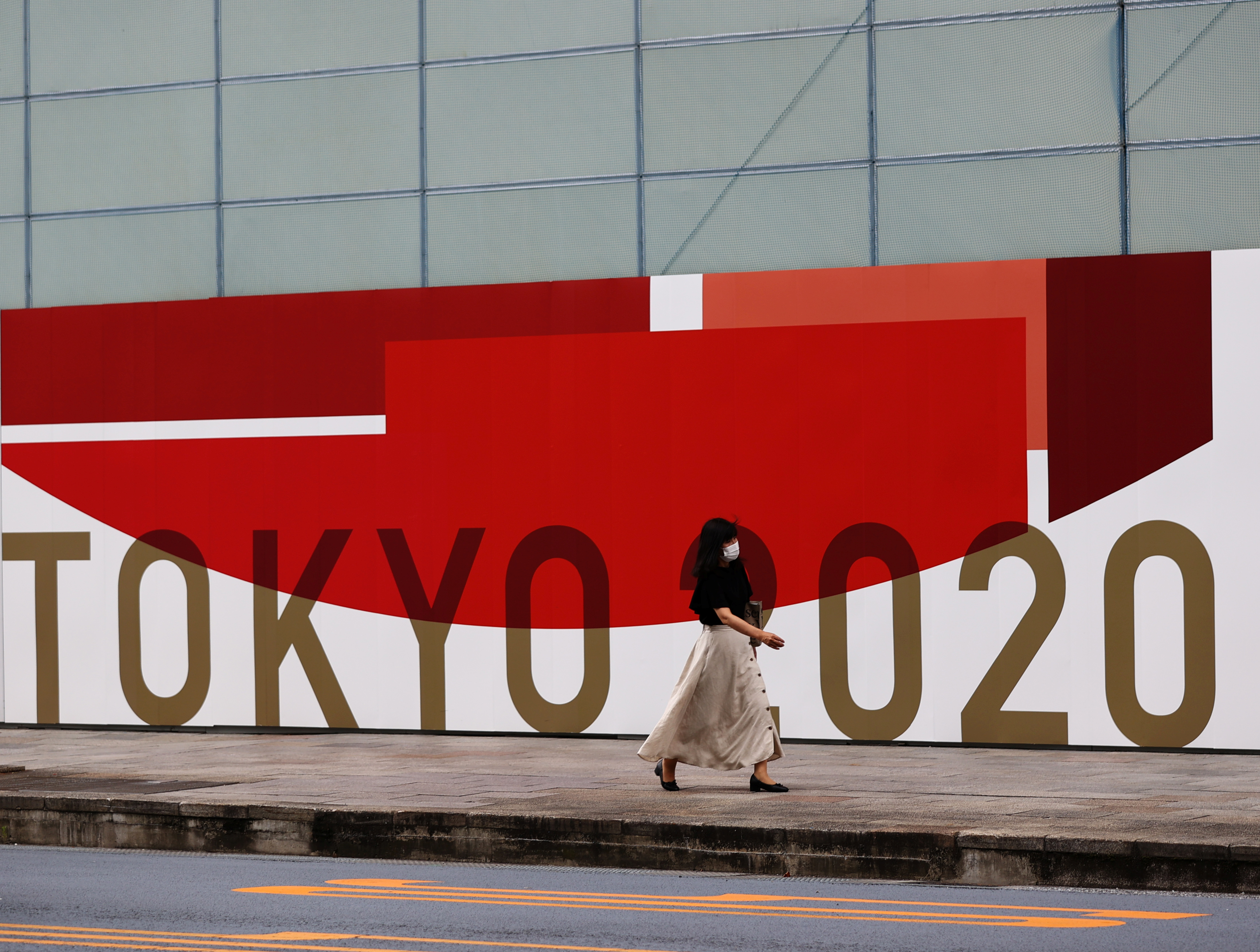 A woman, wearing a protective mask against COVID-19, walks past a wall bearing logo of Tokyo 2020 Olympic Games in Tokyo, Japan, July 29, 2021. REUTERS/Kim Kyung-Hoon