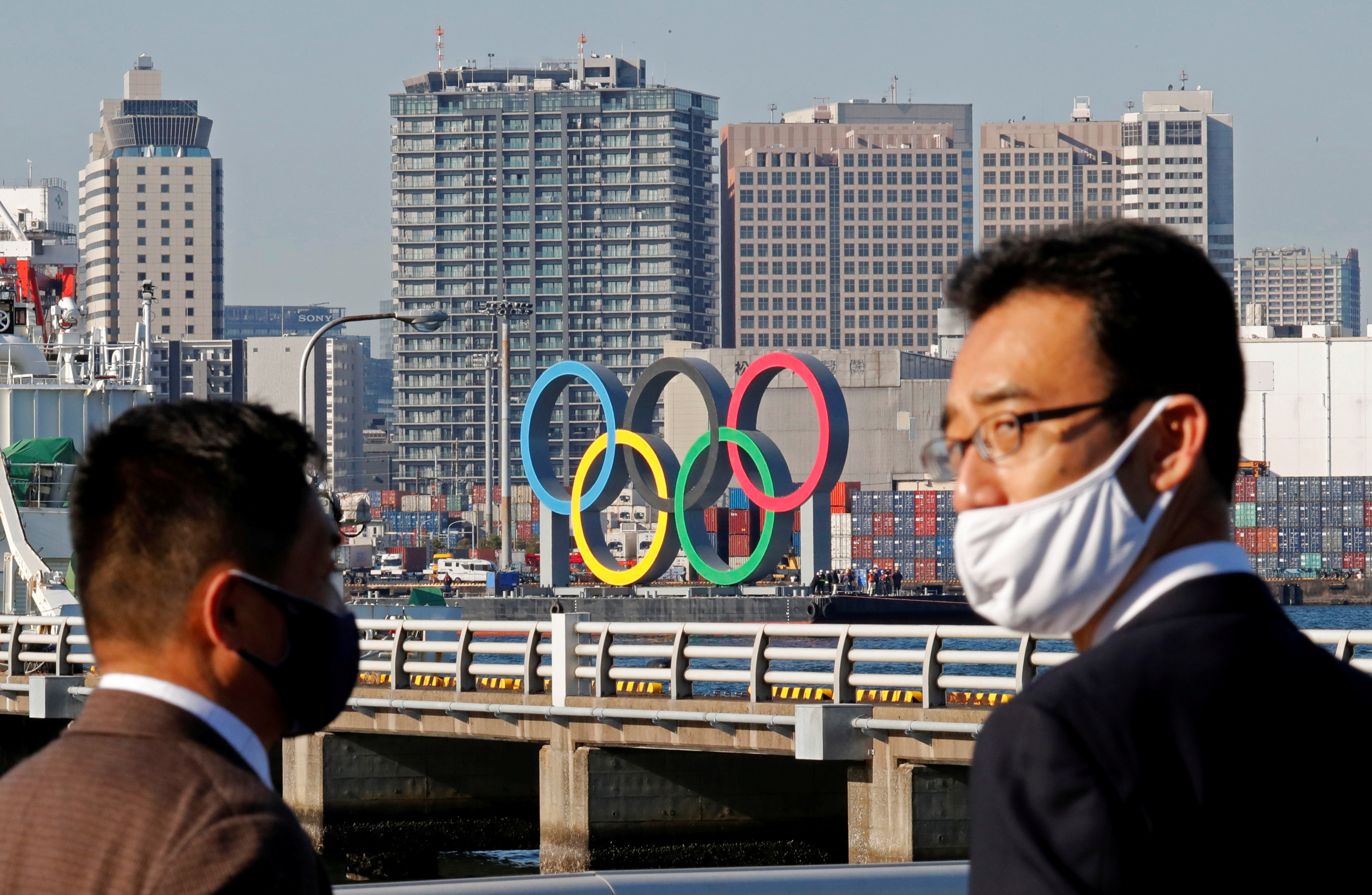 Men wearing face masks watch as giant Olympic rings, which were temporarily taken down in August for maintenance amid the coronavirus disease (COVID-19) outbreak, are transported for reinstallation at the waterfront area at Odaiba Marine Park in Tokyo, Japan December 1, 2020. REUTERS/Kim Kyung-Hoon/File Photo