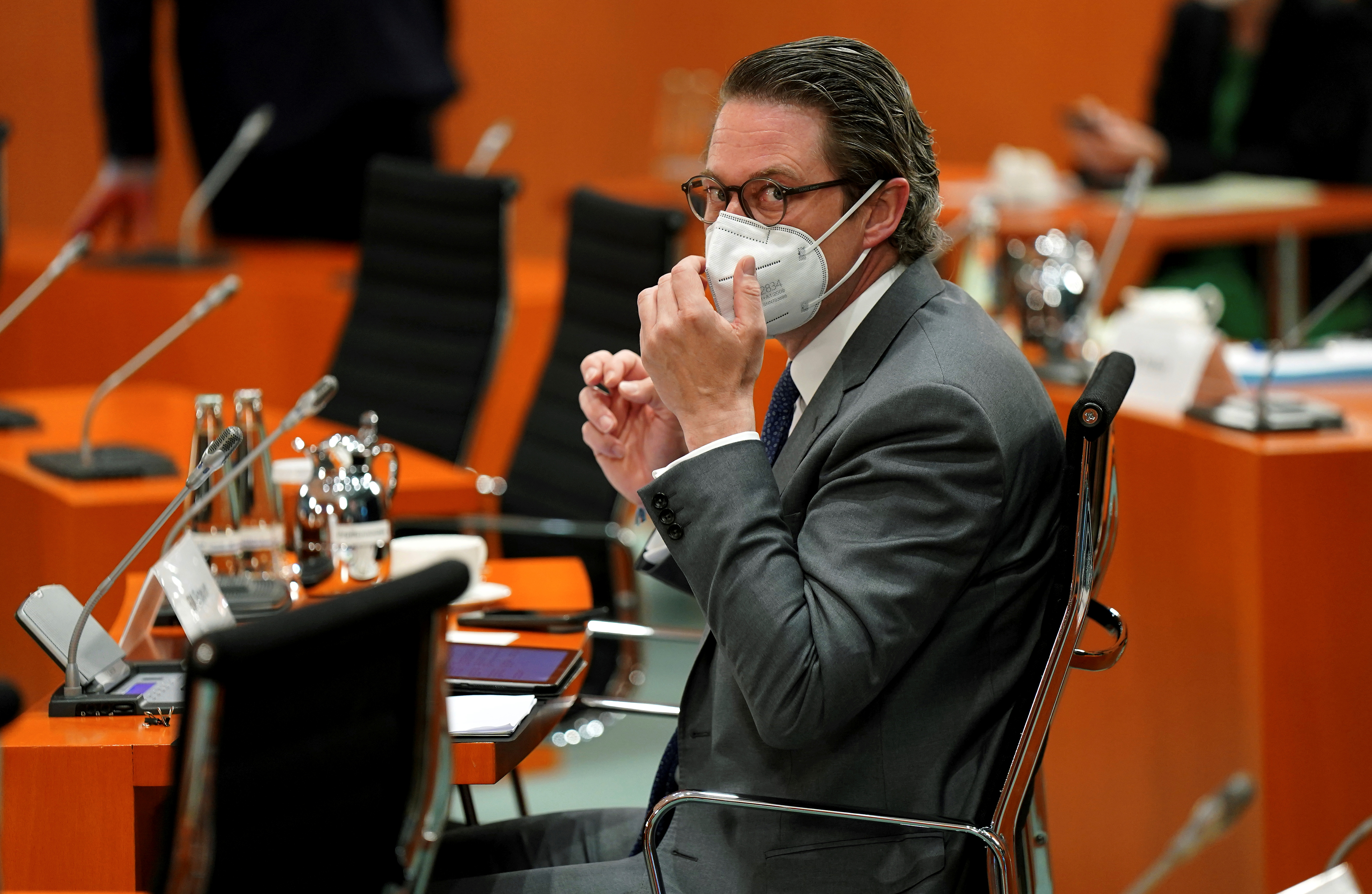 German Transport Minister Andreas Scheuer adjusts his face mask as he attends the weekly cabinet meeting at the Chancellery in Berlin, Germany May 12, 2021. Michael Sohn/Pool via REUTERS