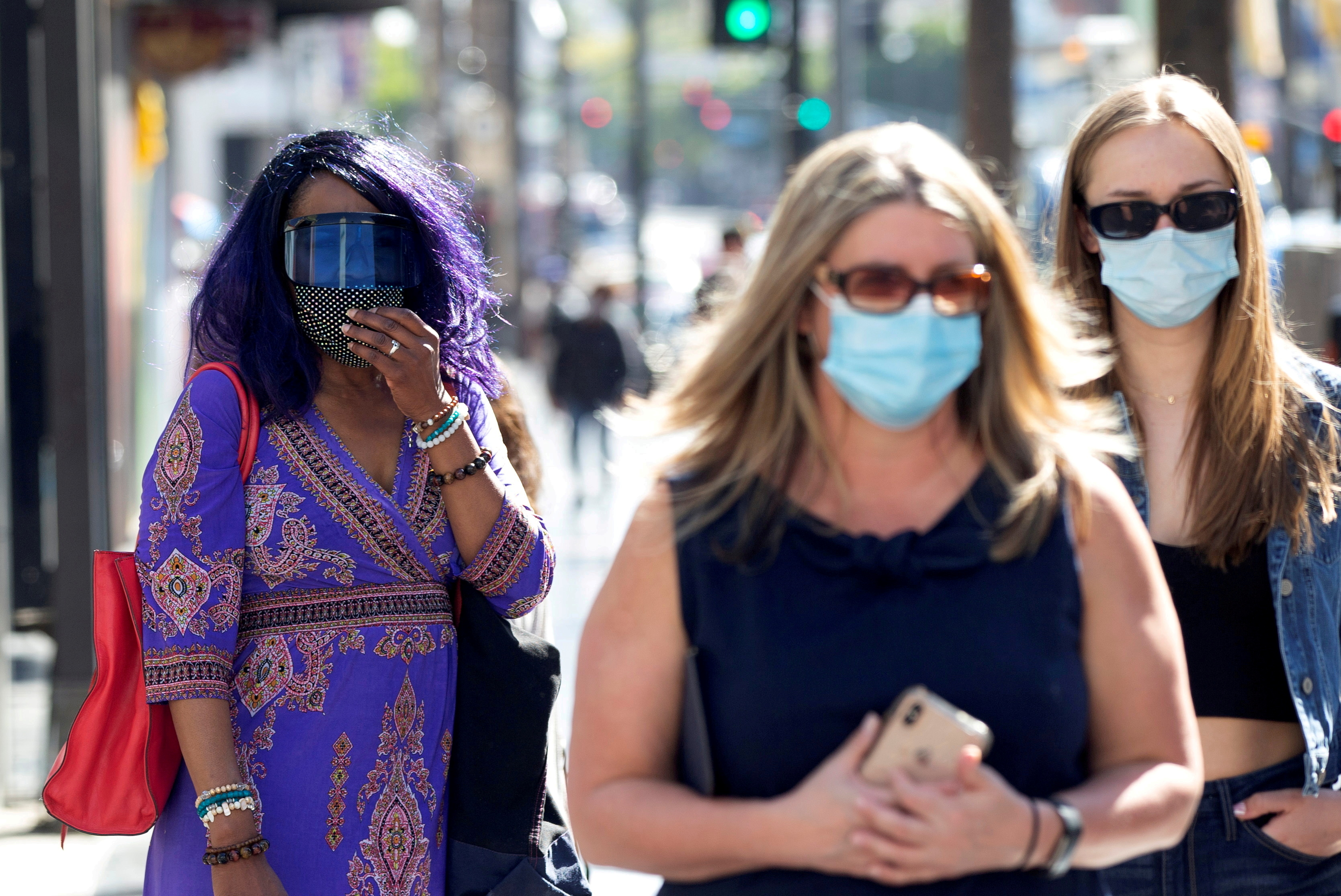 People wearing face protective masks walk on Hollywood Blvd during the outbreak of the coronavirus disease (COVID-19), in Los Angeles, California, U.S., March 29, 2021.  REUTERS/Mario Anzuoni/File Photo