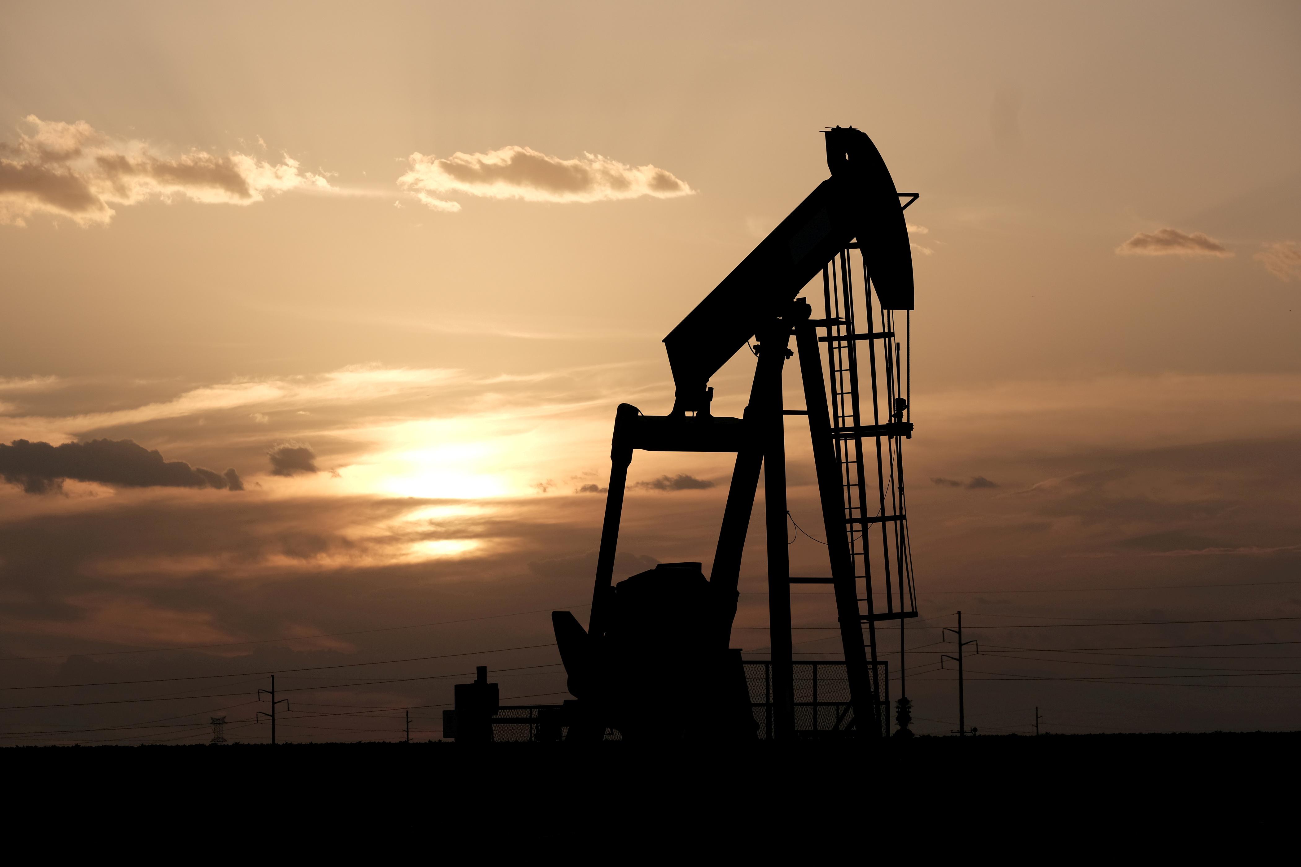 Oil pump jacks work at sunset near Midland, Texas, U.S., August 21, 2019. REUTERS/Jessica Lutz/File Photo