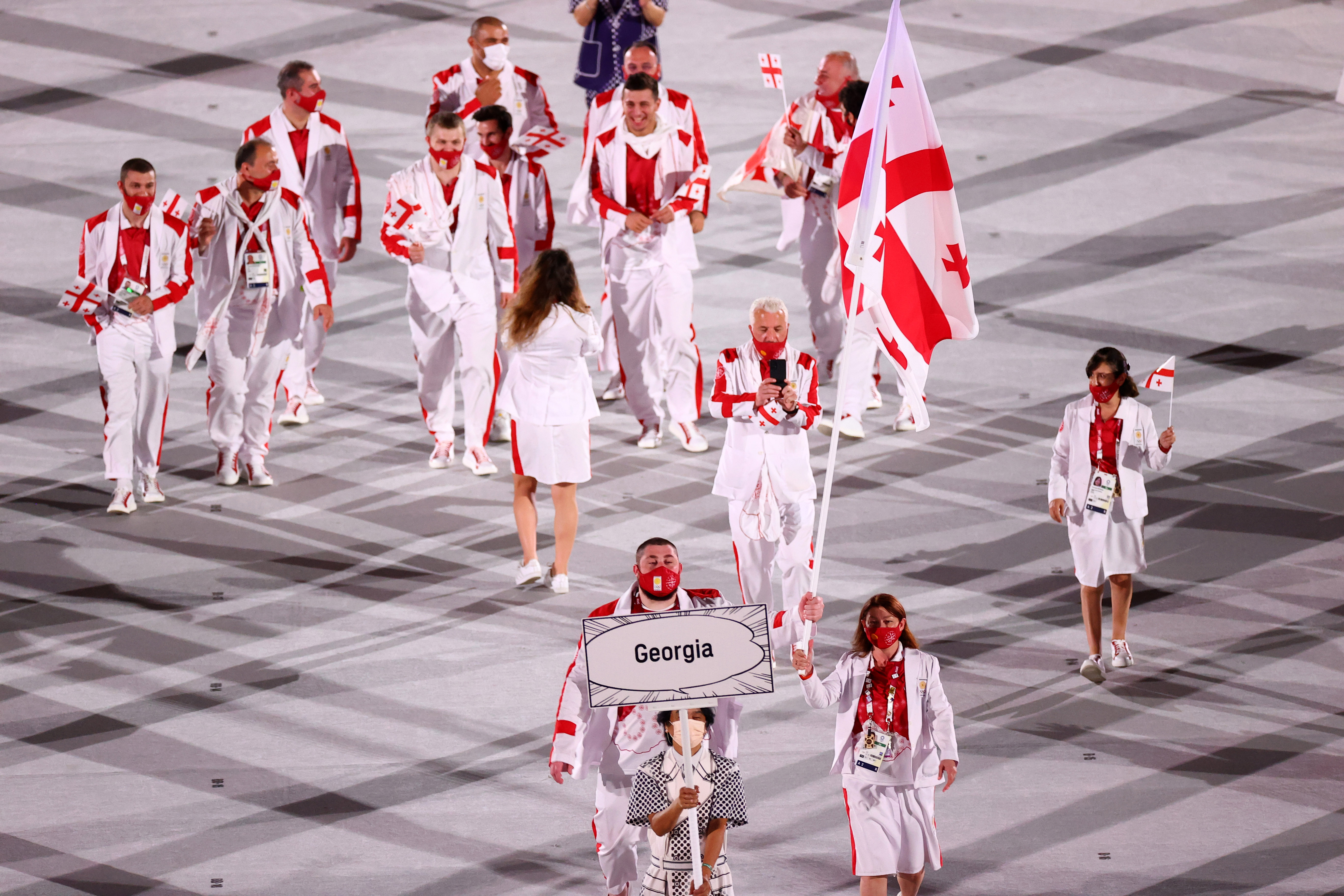 Tokyo 2020 Olympics - The Tokyo 2020 Olympics Opening Ceremony - Olympic Stadium, Tokyo, Japan - July 23, 2021. Flag bearers Nino Salukvadze of Georgia and Lasha Talakhadze of Georgia lead their contingent during the athletes parade at the opening ceremony REUTERS/Mike Blake