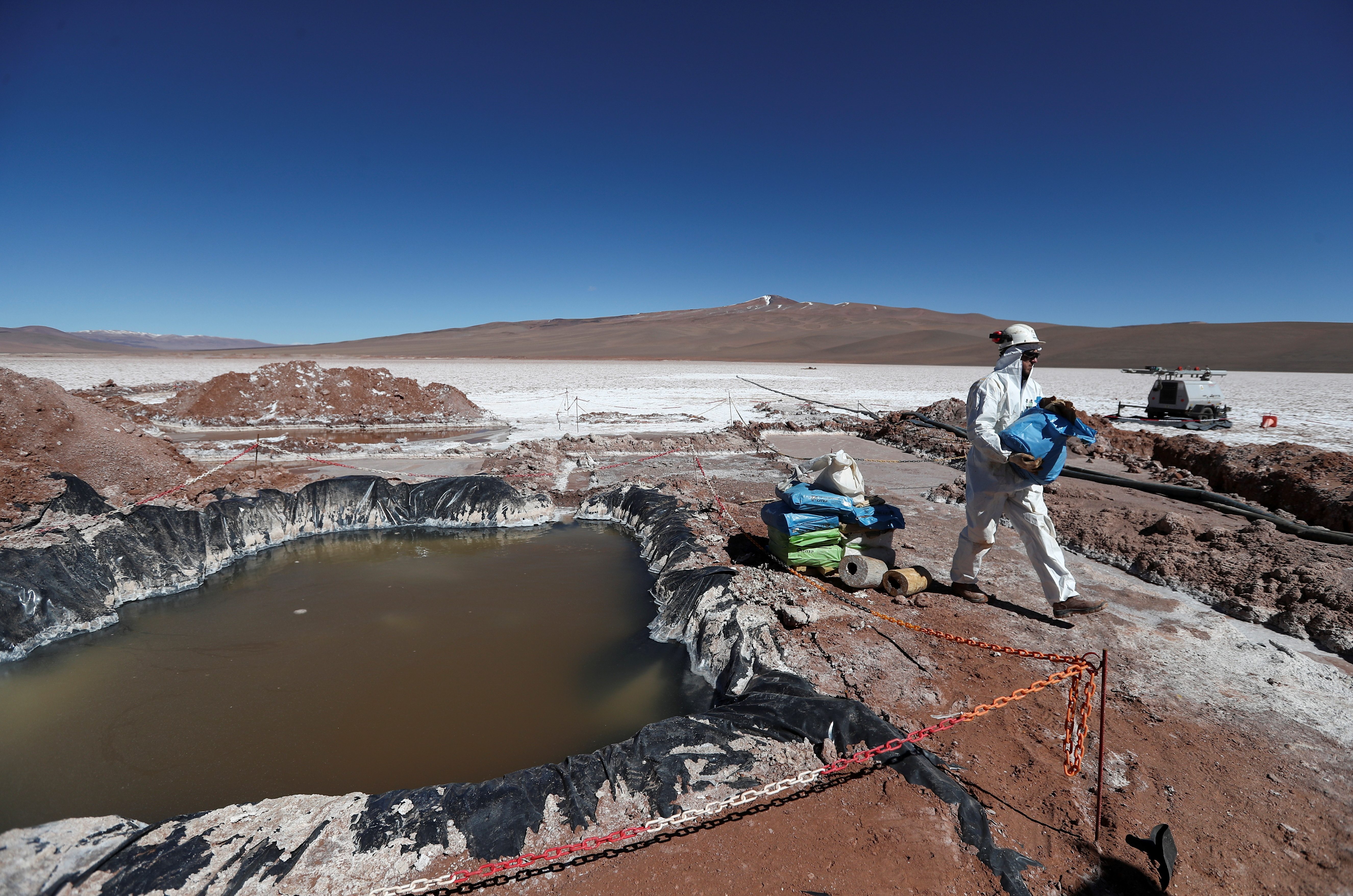 An Alpha lithium employee works next to a brine pool at the Tolillar salt flat, in Salta, Argentina August 13, 2021. REUTERS/Agustin Marcarian