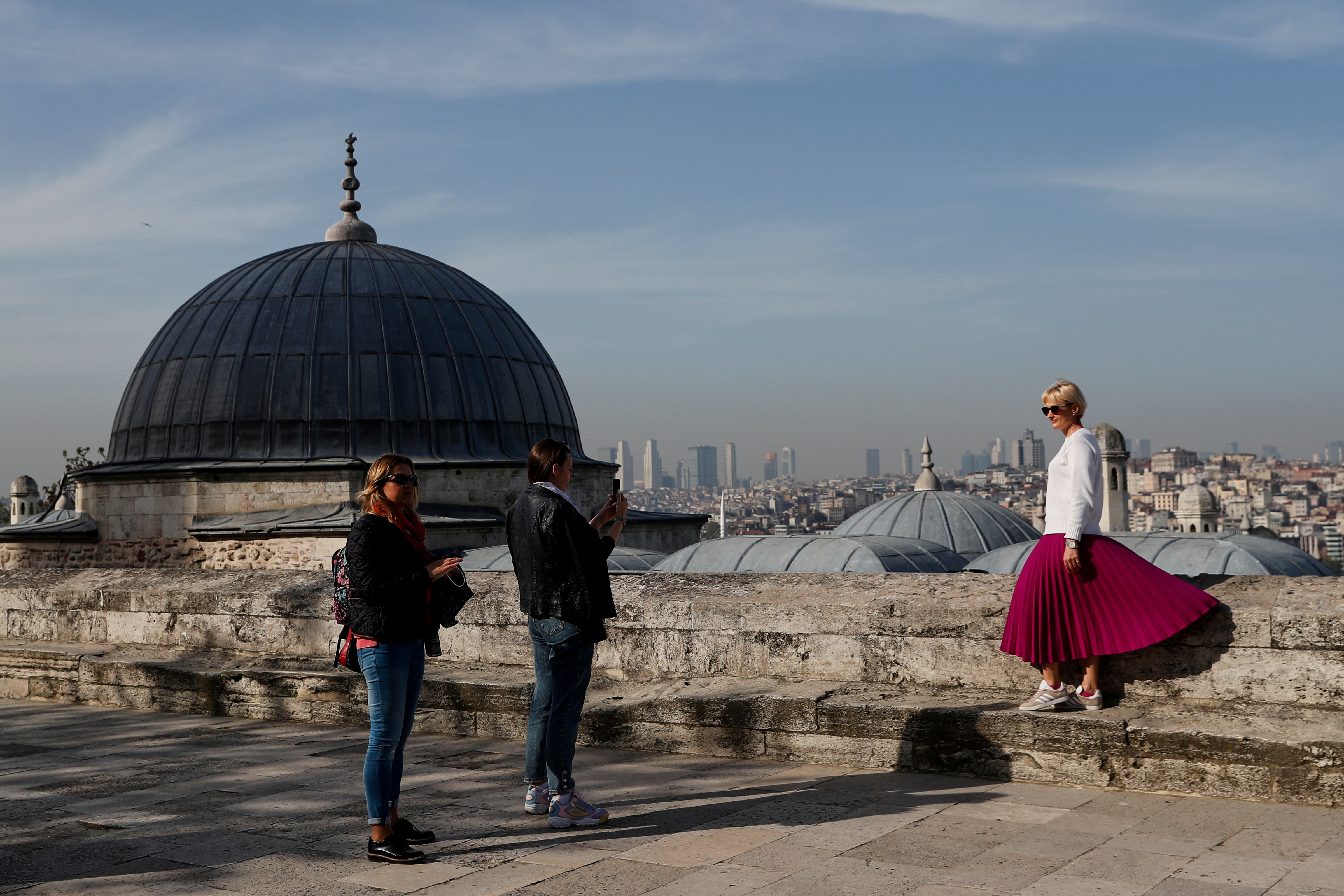 A tourist poses for a souvenir photo outside the historic Suleymaniye Mosque in Istanbul, Turkey, during a nationwide lockdown of the local population imposed to slow the spread of the coronavirus, April 30, 2021. REUTERS/Murad Sezer