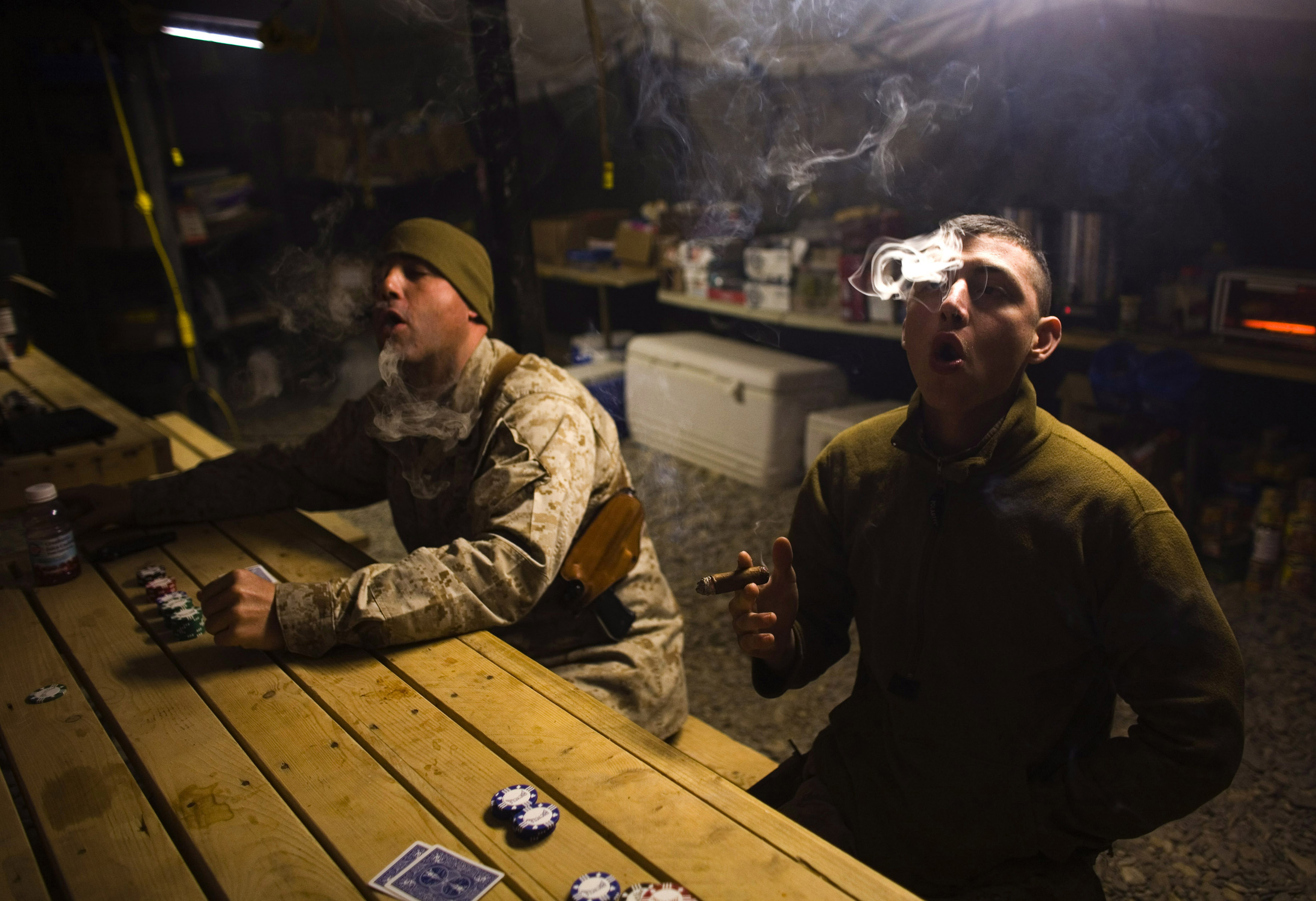 U.S. Marines from MP Company, 1st Marine Division attached to 3rd Battalion 4th Marines, smoke cigars as they play cards at AHP station in Nimroz province, southern Afghanistan January 14, 2010. REUTERS/Stringer