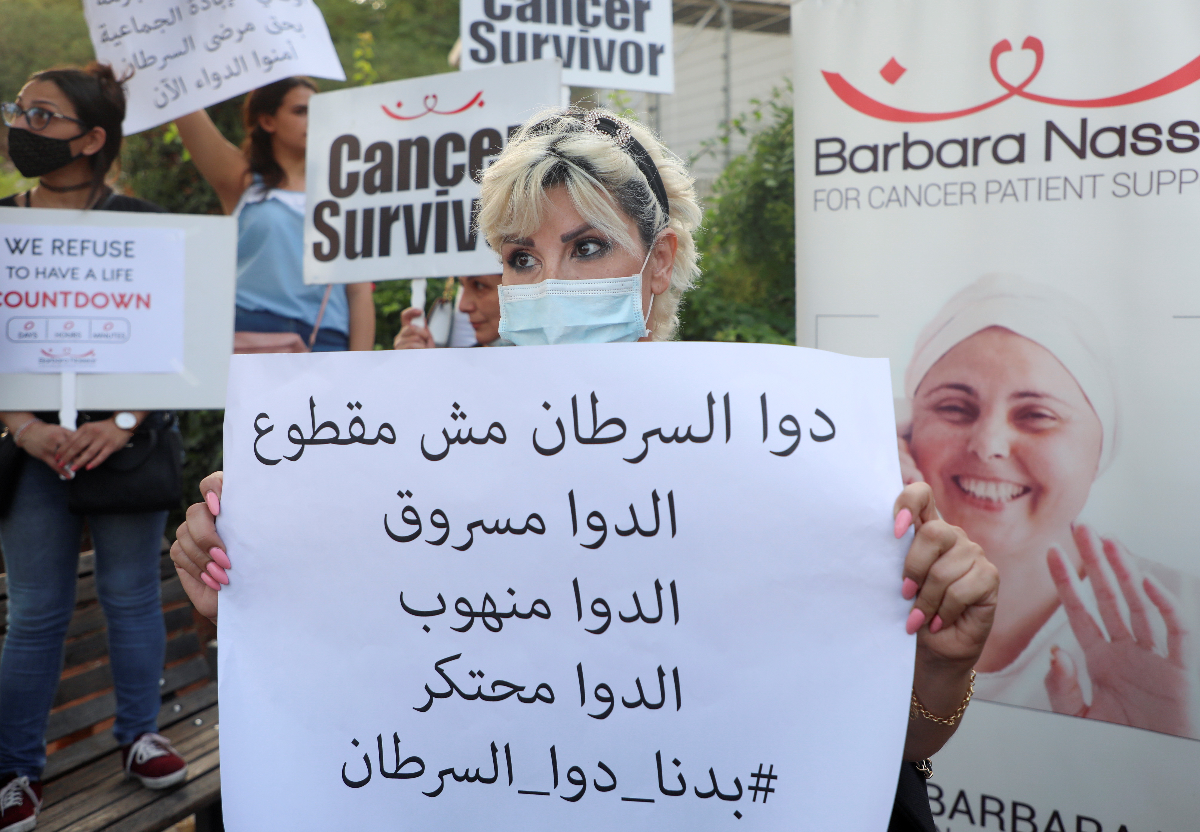 Christine Tohme, a cancer patient, holds a sign during a sit-in demonstration as shortages of cancer medications spread, in front of the U.N. headquarters in Beirut, Lebanon August 26, 2021.  REUTERS/Mohamed Azakir The banner reads: