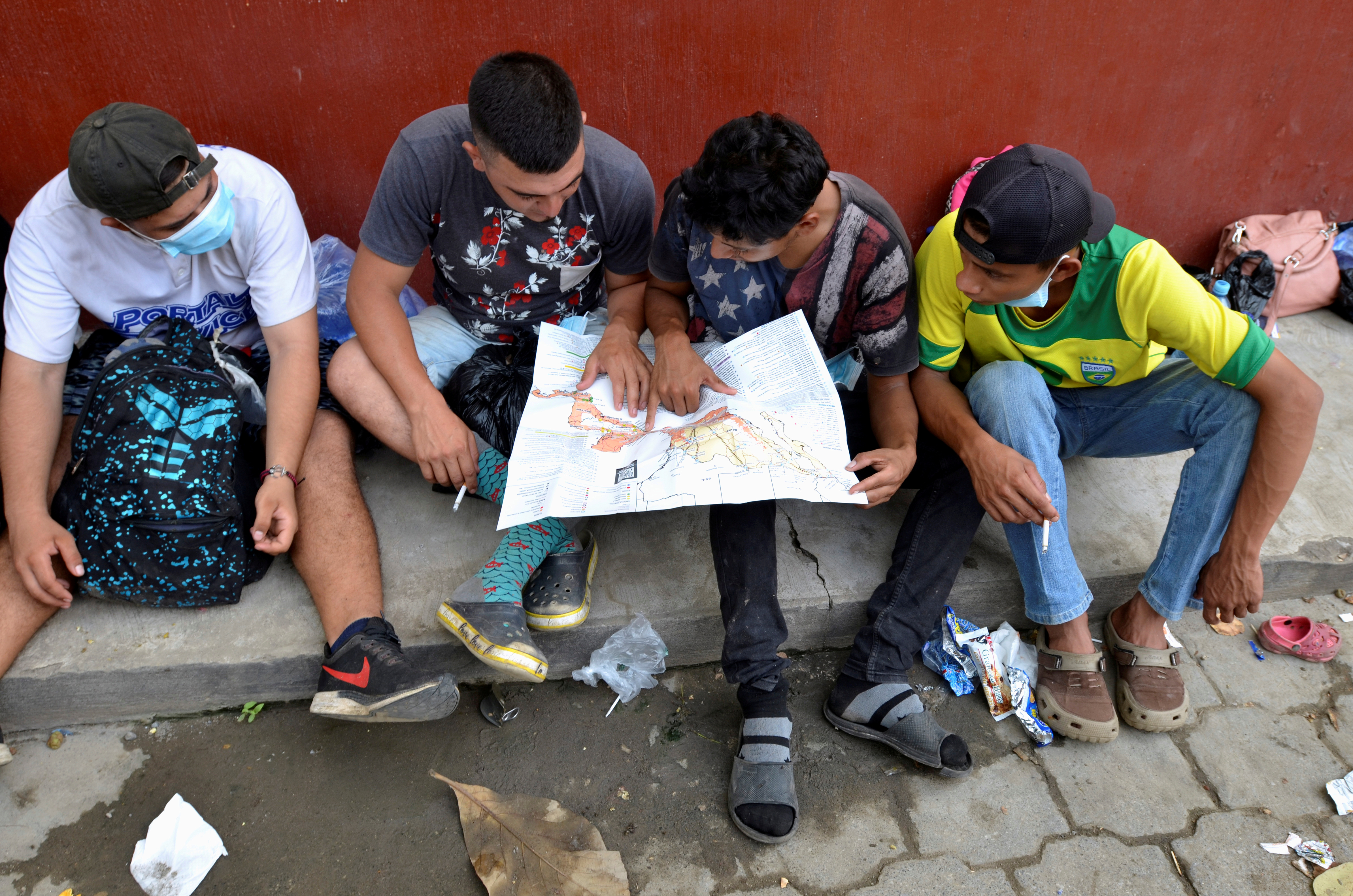 A group of Honduran migrants who are trying to reach the U.S. , look at a Central America and Mexico map outside a migrant shelter as they wait to move towards the Guatemala and Mexico border, in Tecun Uman, Guatemala October 3, 2020. REUTERS/Jose Torres/