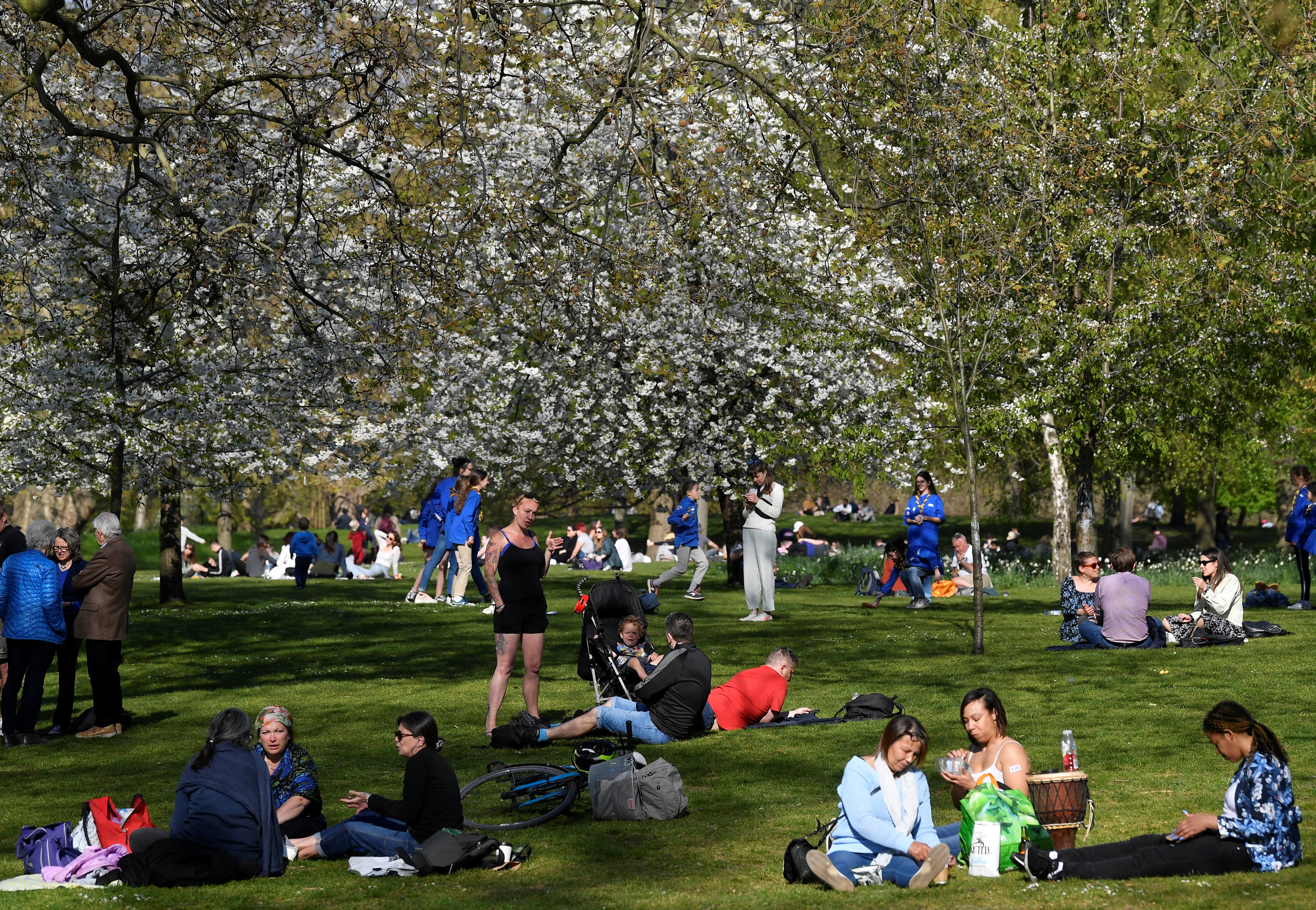 People relax in the sunshine, as lockdown restrictions are eased amidst the spread of the coronavirus disease (COVID-19) pandemic in St. James's Park, London, Britain, April 24, 2021. REUTERS/Toby Melville