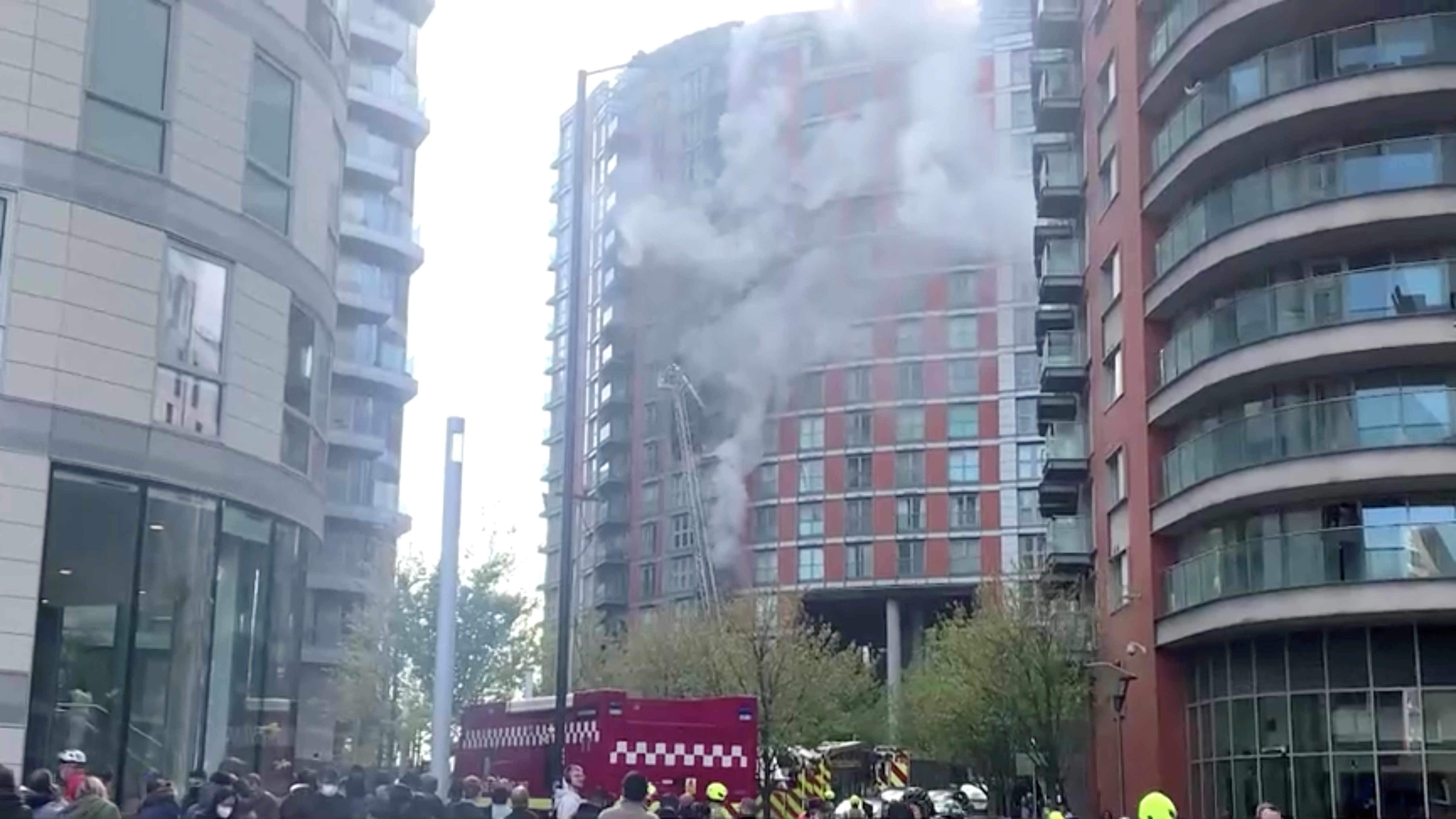 Firefighters work to put out the flames at the cladding panel-covered Tower Hamlets, New Providence Wharf in East London, Britain May 7, 2021 in this still image taken from social media video. Twitter @iamclaricelin via REUTERS