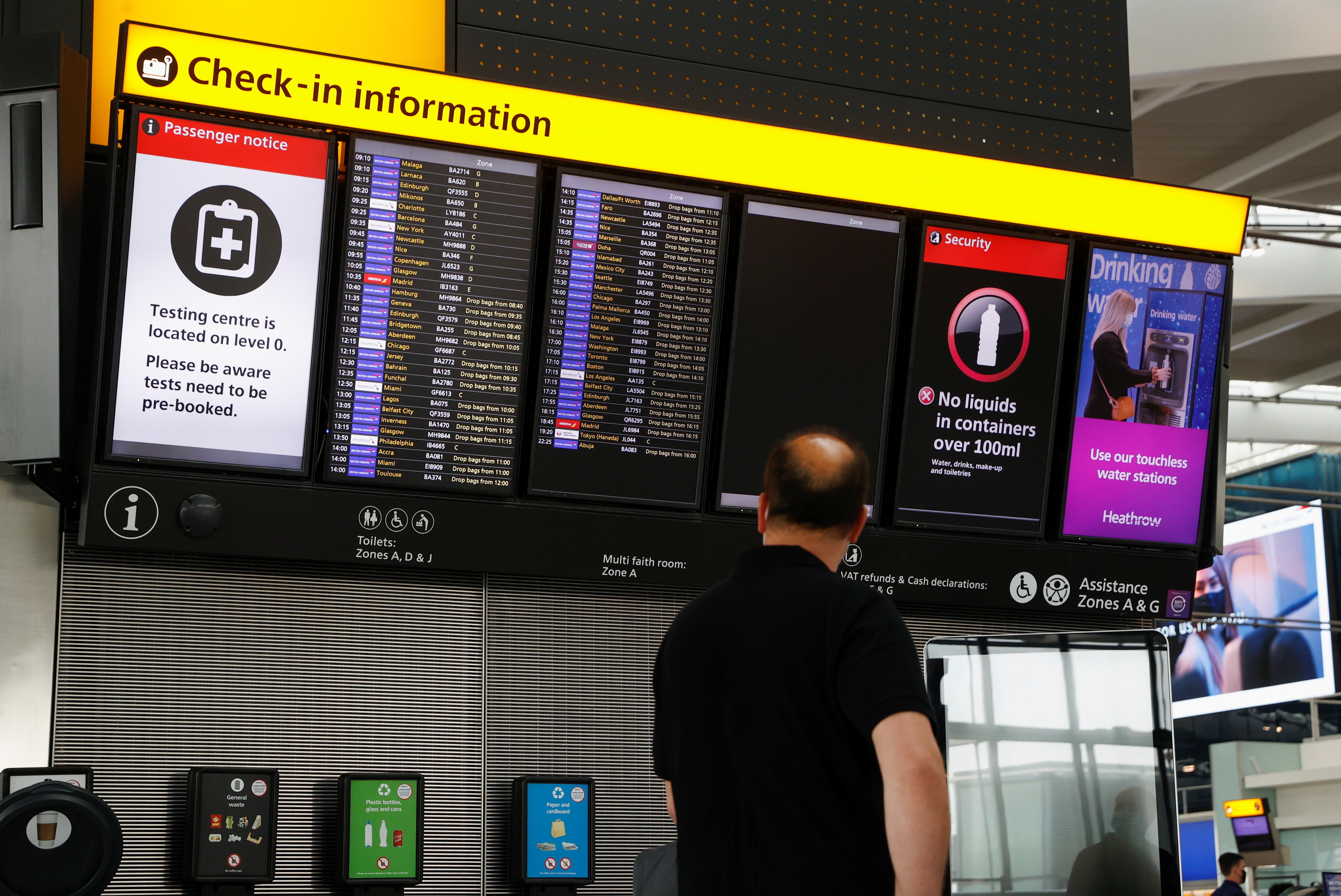 A man looks at a check-in information board in the departures area of Terminal 5 at Heathrow Airport in London, Britain, May 17, 2021. REUTERS/John Sibley