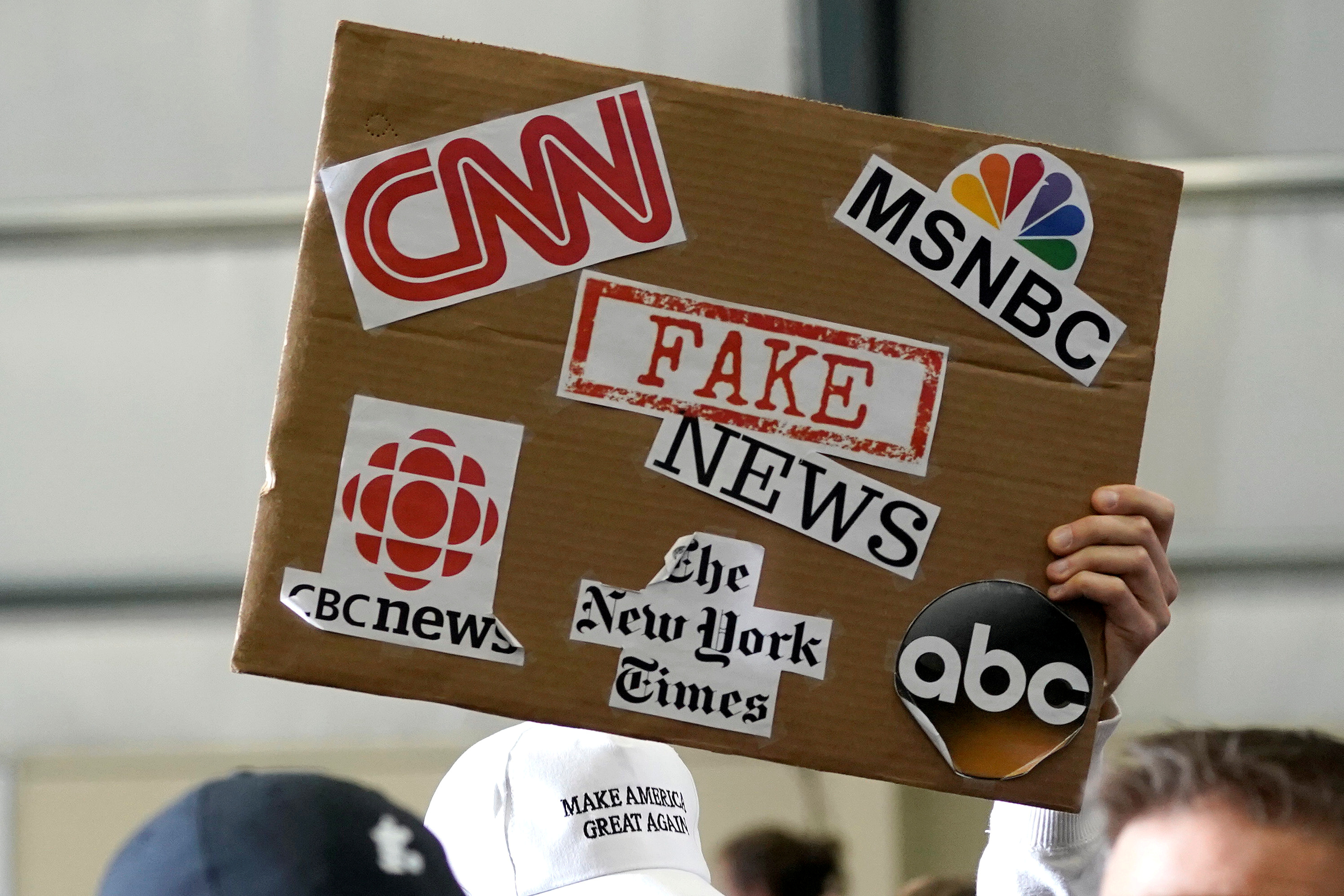 A sign showing major news organizations along with the words