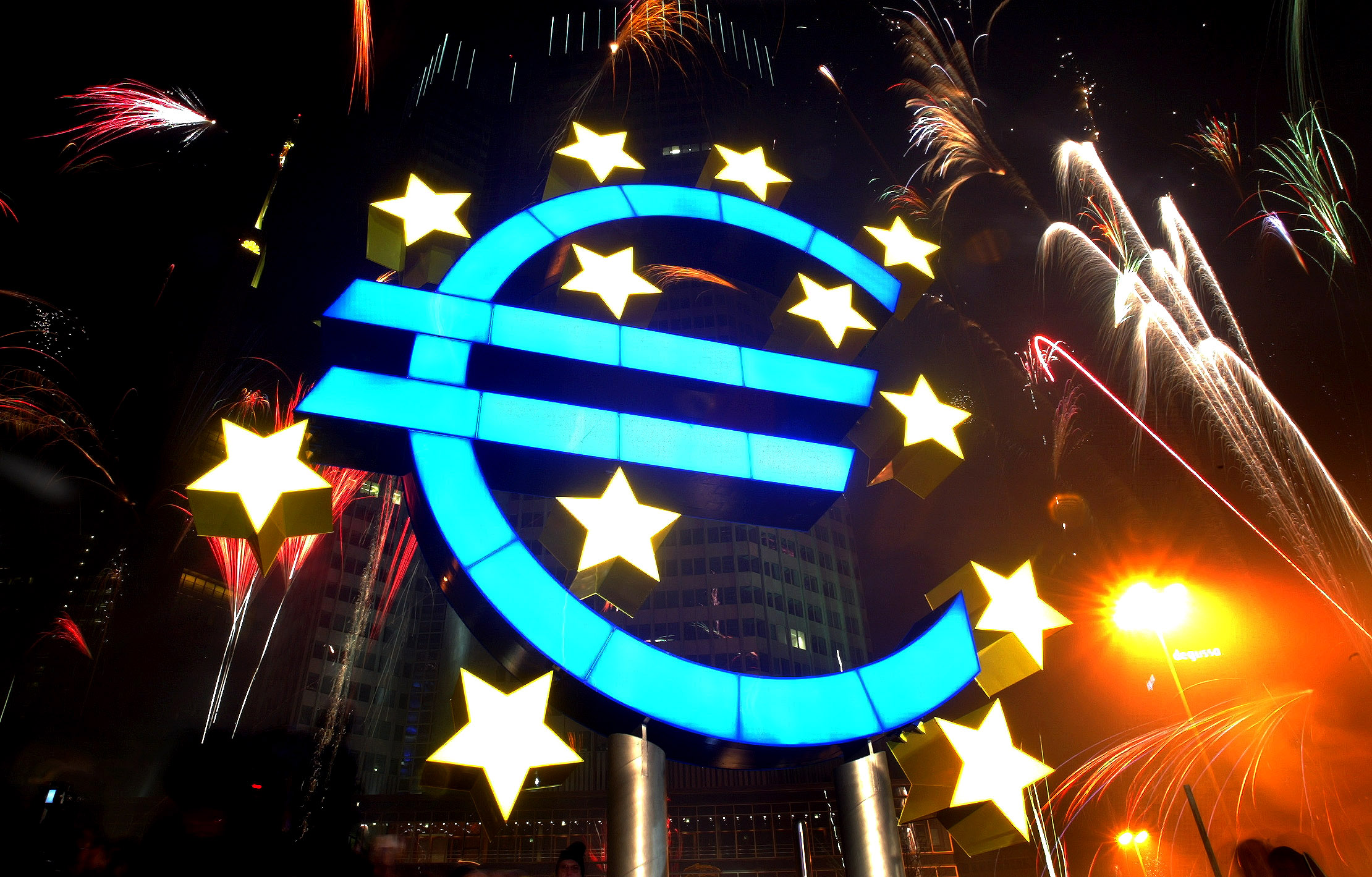 Fireworks illuminate the sky around a huge euro sculpture, designed by German artist Ottmar Hoerl, in front of the headquarters of the European Central Bank (ECB) in Frankfurt, January 1, 2002.