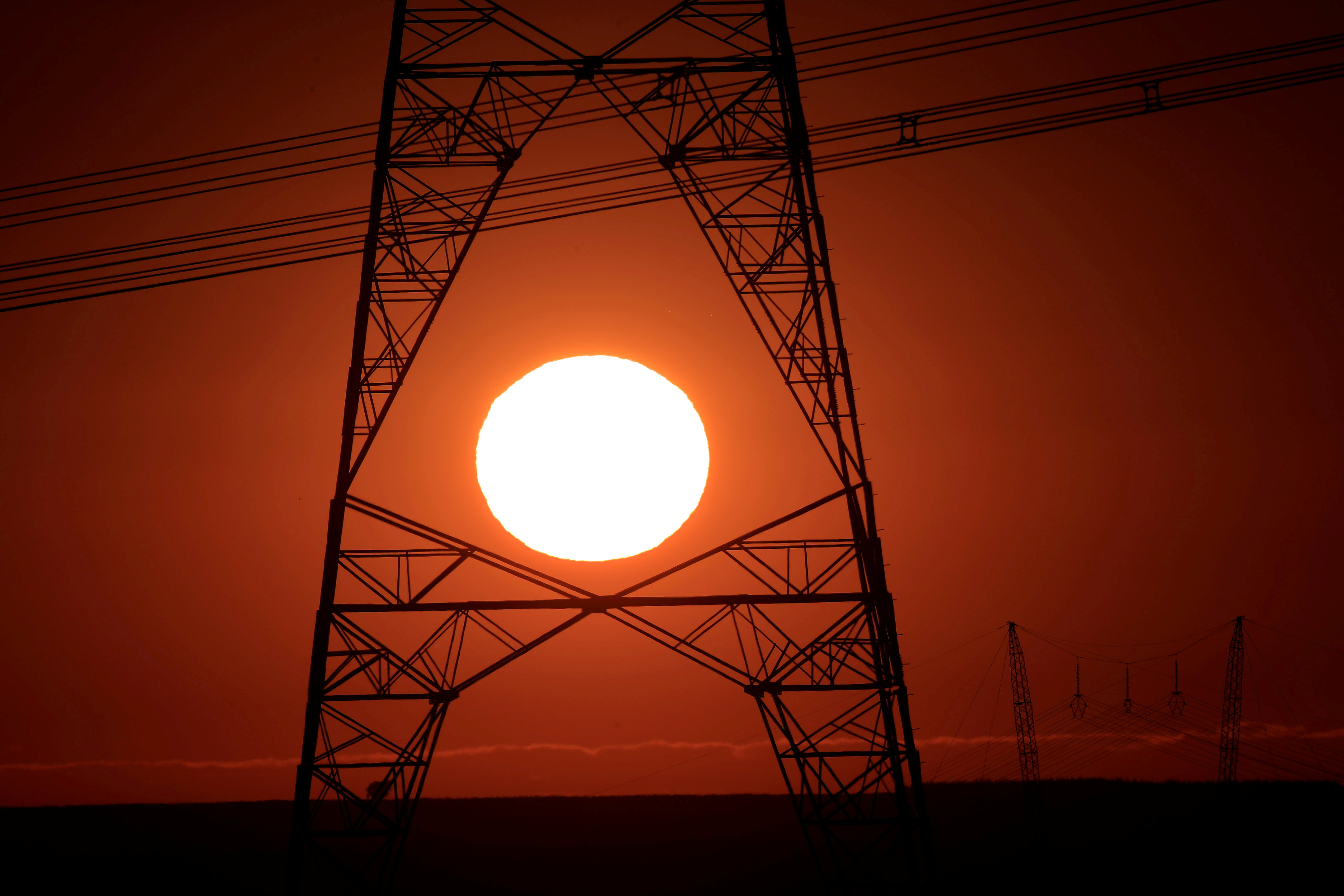 Power lines connecting pylons of high-tension electricity are seen during sunrise near Brasilia, Brazil August 29, 2018. Picture taken August 29, 2018. REUTERS/Ueslei Marcelino/File Photo
