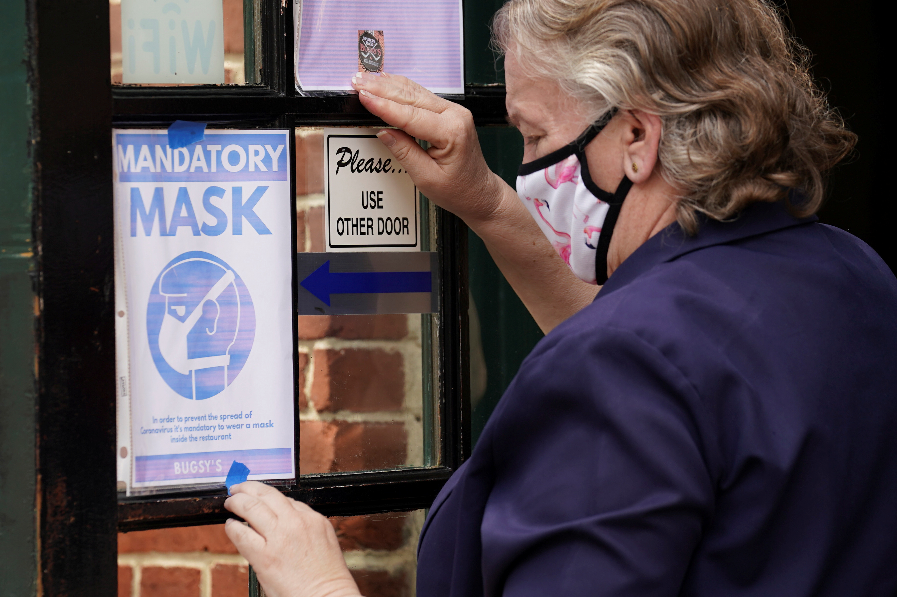 As Phase One of reopening begins in Northern Virginia today, a restaurant worker in a face mask to protect against the coronavirus (COVID-19) puts up a