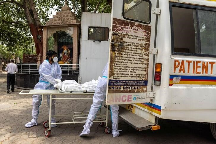 Health workers carry the body of a person, who died from complications related to the coronavirus disease (COVID-19), for cremation at a crematorium in New Delhi, India, June 10, 2021. REUTERS/Danish Siddiqui