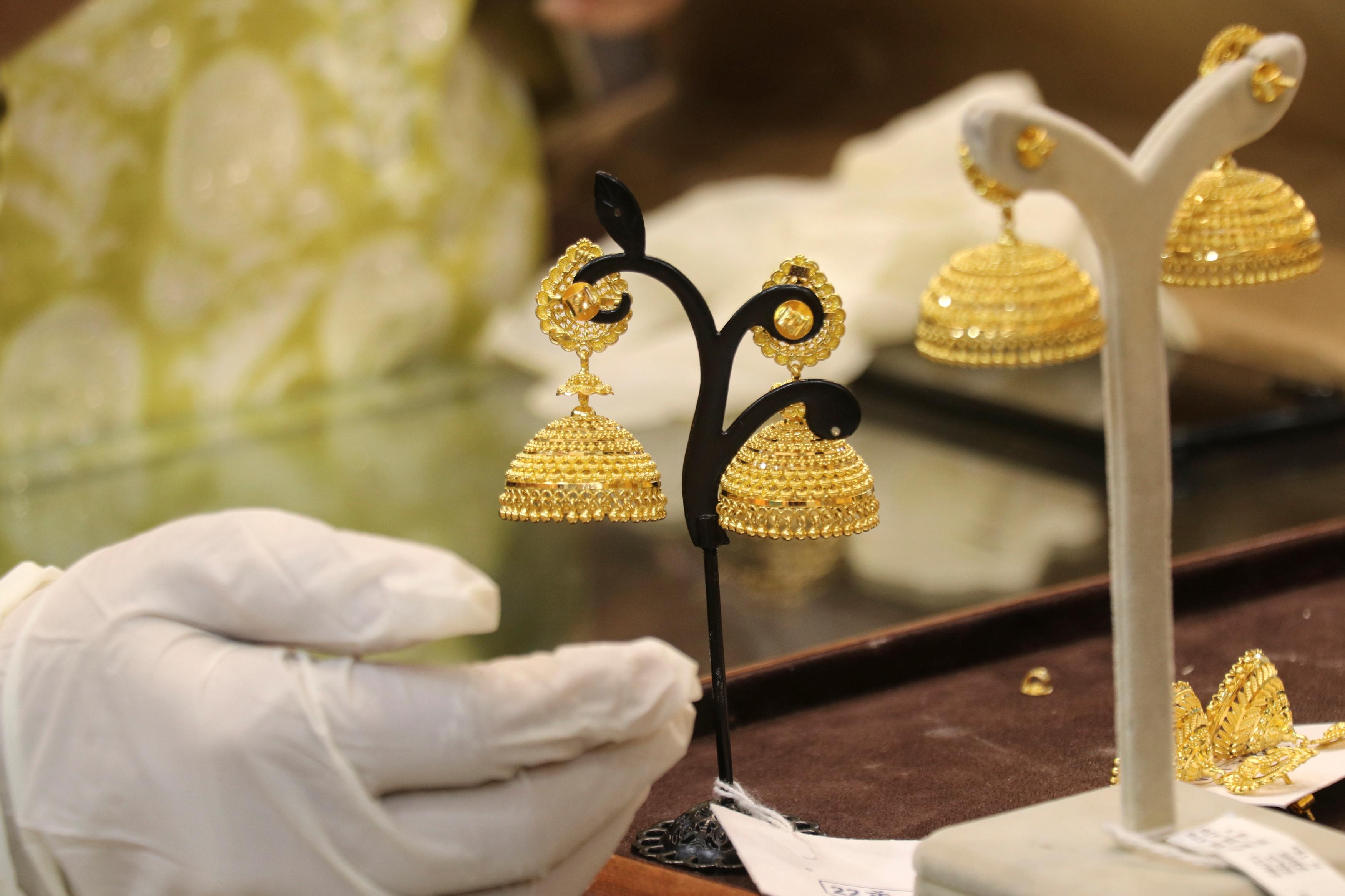 Customer looks at gold earrings at a jewellery showroom during Dhanteras, a Hindu festival associated with Lakshmi, the goddess of wealth, amidst the spread of COVID-19 in Mumbai, India, November 13, 2020. REUTERS/Niharika Kulkarni/File photo