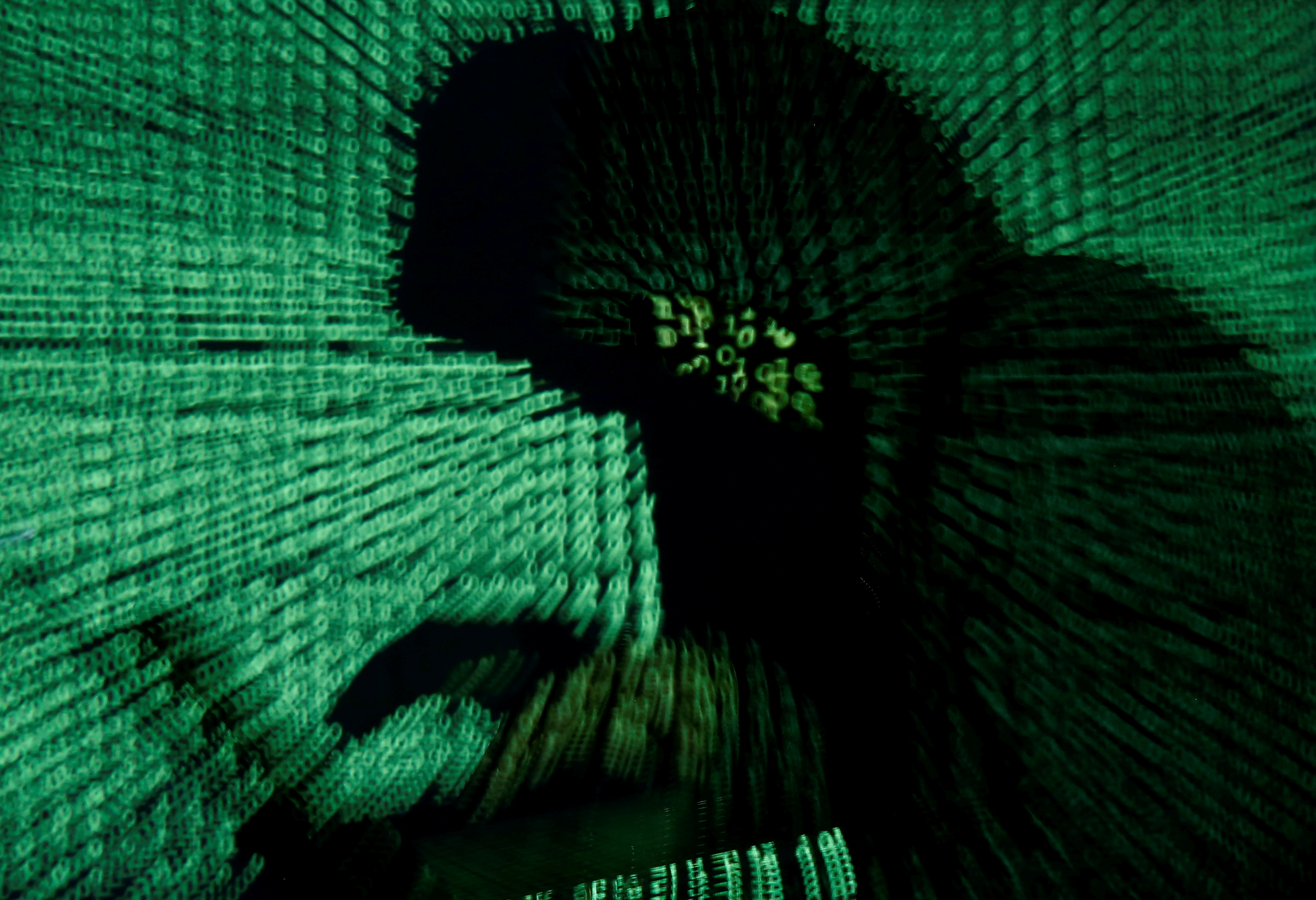 A man holds a laptop computer as cyber code is projected on him in this illustration picture taken on May 13, 2017. Capitalizing on spying tools believed to have been developed by the U.S. National Security Agency, hackers staged a cyber assault with a self-spreading malware that has infected tens of thousands of computers in nearly 100 countries. REUTERS/Kacper Pempel