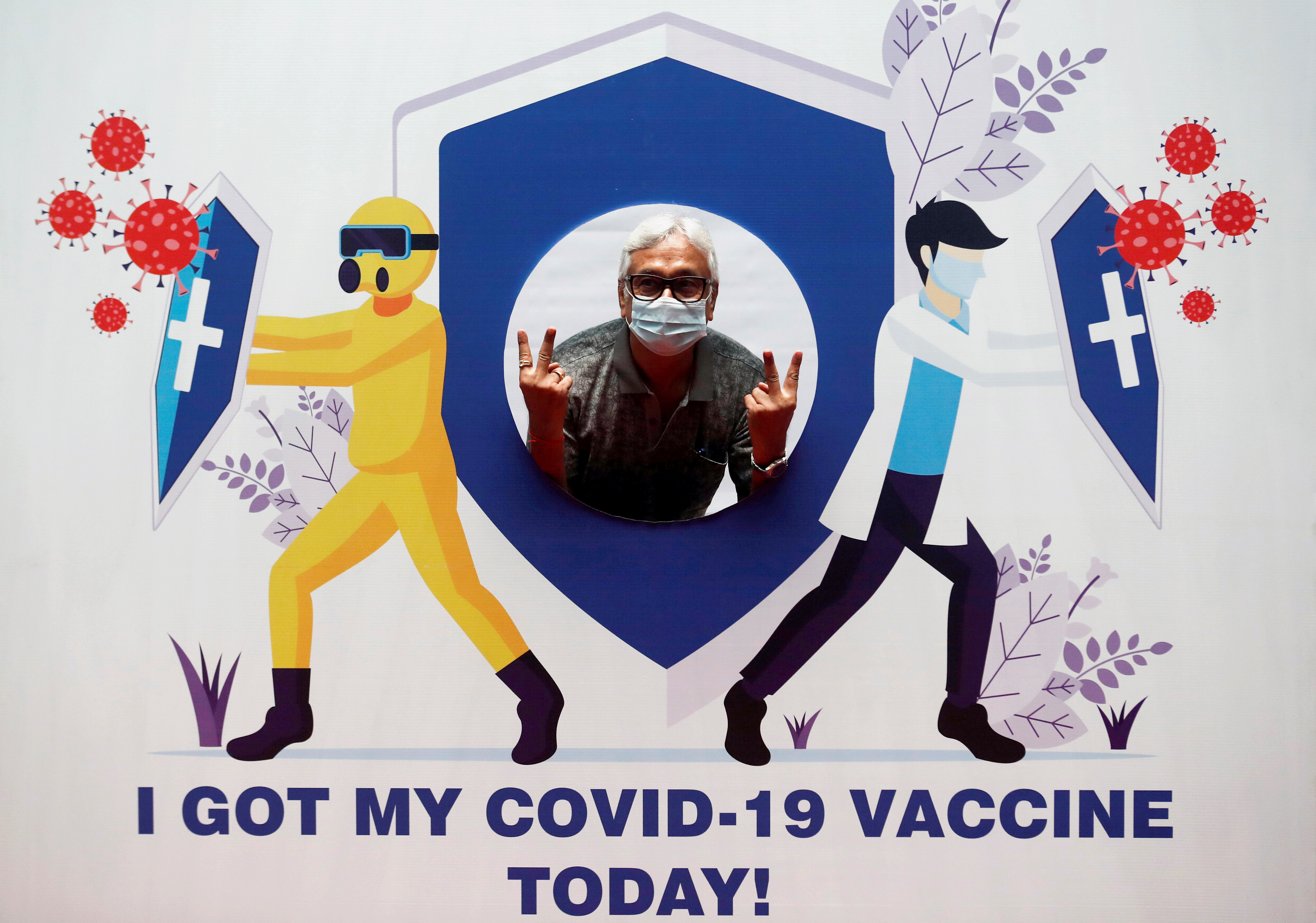 A man poses for a picture with a cardboard cutout after receiving a dose of COVISHIELD, a COVID-19 vaccine manufactured by Serum Institute of India, at a vaccination centre, during the second wave of vaccination for the elderly with comorbidities, amid the spread of the coronavirus disease (COVID-19) in Mumbai, India, March 10, 2021. REUTERS/Francis Mascarenhas/Files