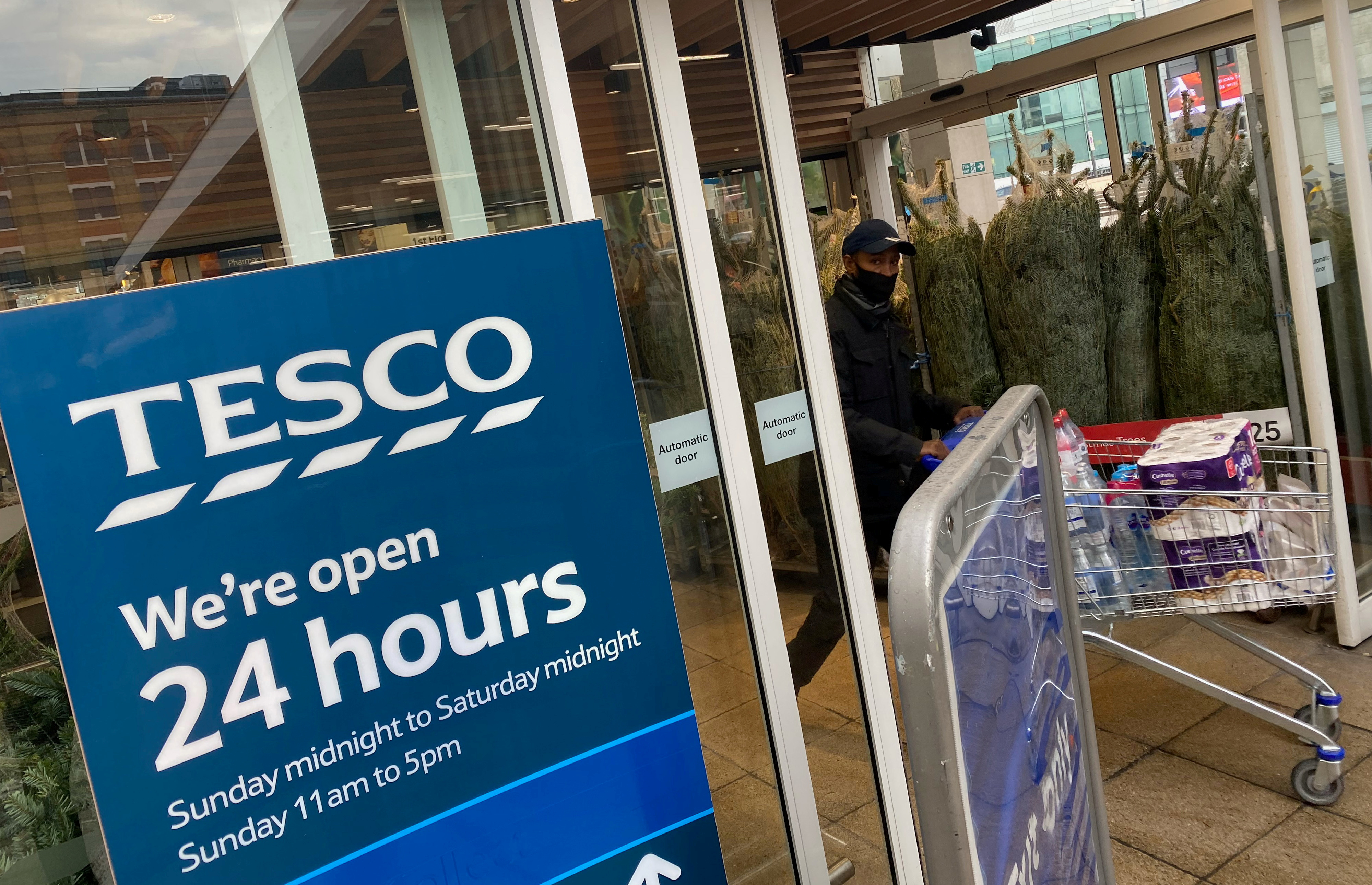 A shopper wearing a protective face-mask passes christmas trees for sale and a sign indicating 24 hour opening times at a Tesco supermarket amid the spread of the coronavirus disease (COVID-19), London, Britain, December 6, 2020. REUTERS/Toby Melville/File Photo