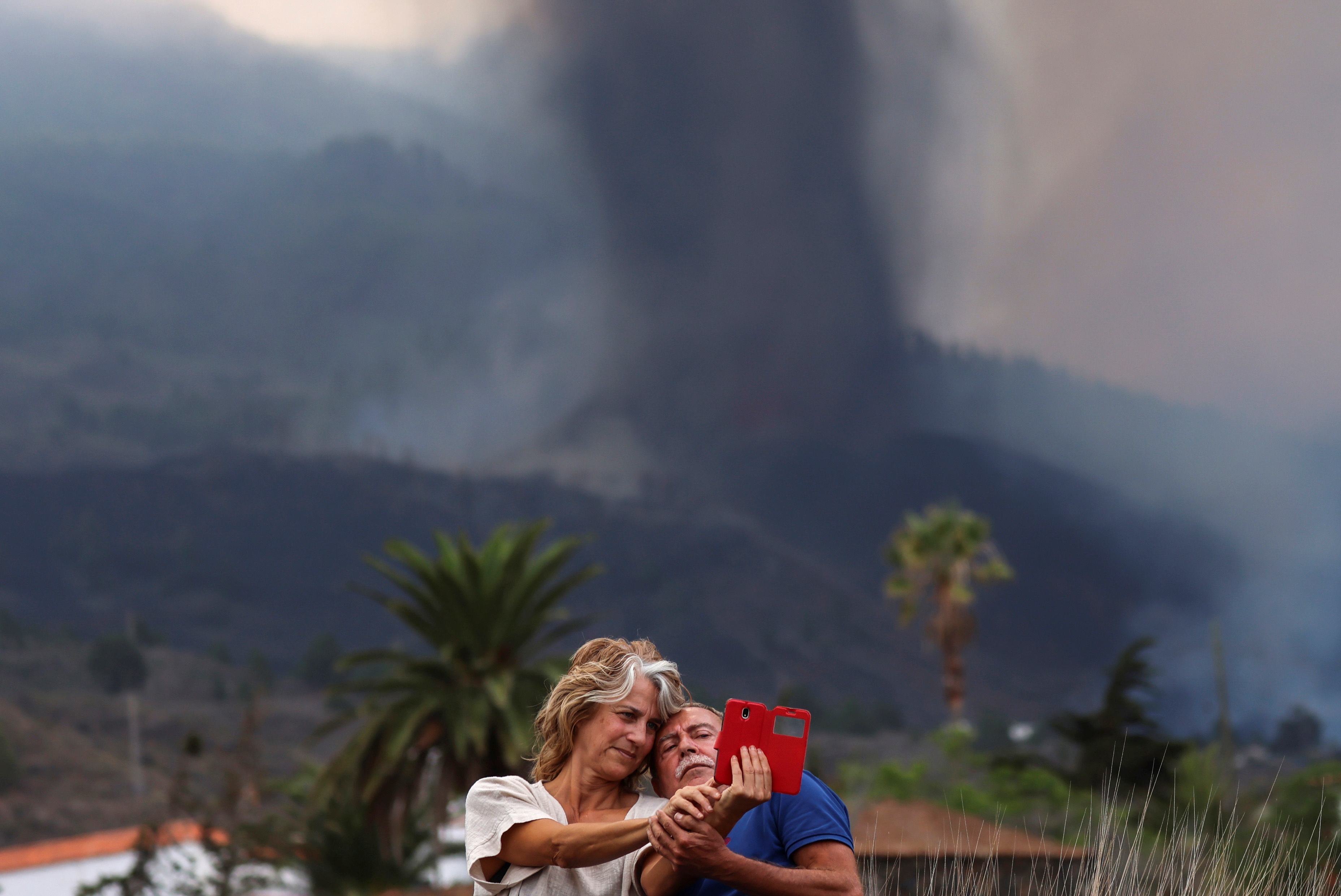 A couple takes a selfie in front of the erupting volcano, in Los Llanos de Aridane on the Canary Island of La Palma, Spain September 20, 2021. REUTERS/Nacho Doce