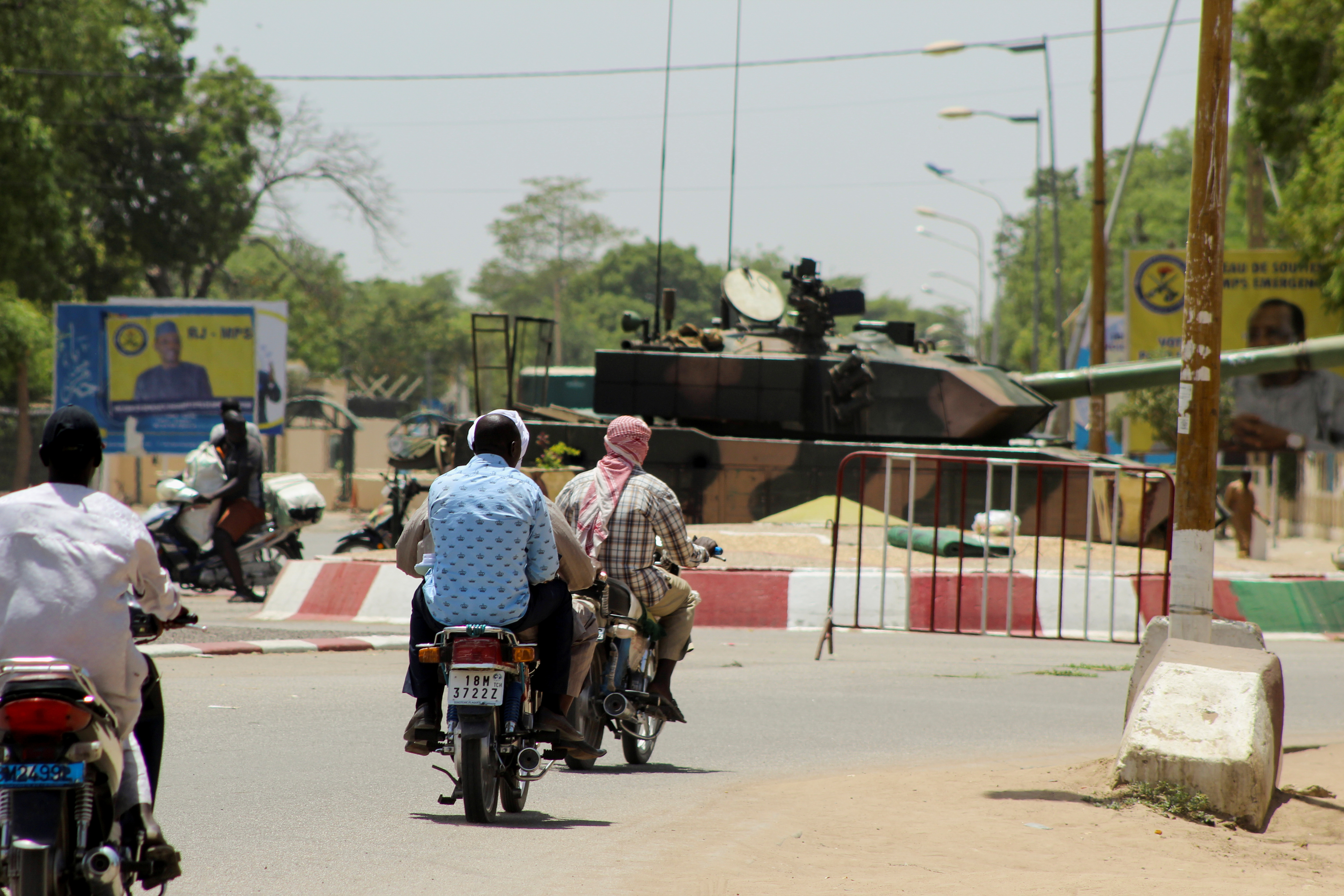 People drive past a Chad army tank near the presidential palace, after Chad's President Idriss Deby, who ruled the country for more than 30 years and was an important Western ally, was killed on the frontline in a battle against rebels in the north, in N'djamena, Chad  April 20, 2021.  REUTERS/Oredje Narcisse